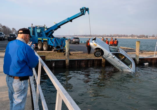 A man takes a video on his cell phone as crews work to remove a car from the St. Clair River near Junction Buoy in Marysville Saturday, April 6, 2019. The driver went to adjust the parking of the vehicle, and it rolled into the river. The vehicle floated down the river a ways before it and the driver went under. The driver later died.
