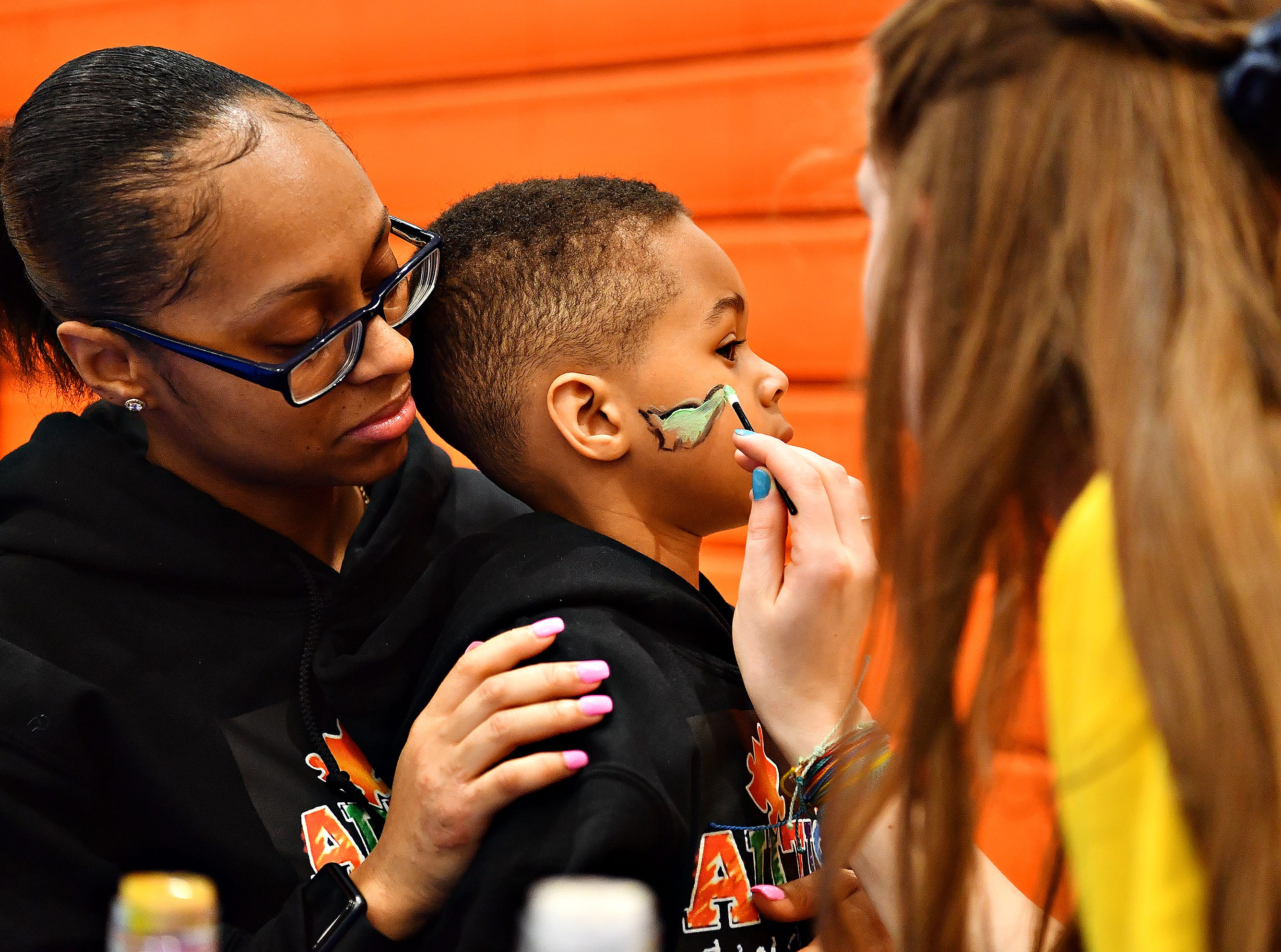 Volunteer Grace Wills, 15, right, of Manchester Township, paints a dinosaur on the face of Jordan Brown, 5, while his mother, Blaire Wright, of Manchester Township, holds him during the 2019 Walk for Autism & Autism Expo at Central York High School in Springettsbury Township, Saturday, April 6, 2019. Dawn J. Sagert photo