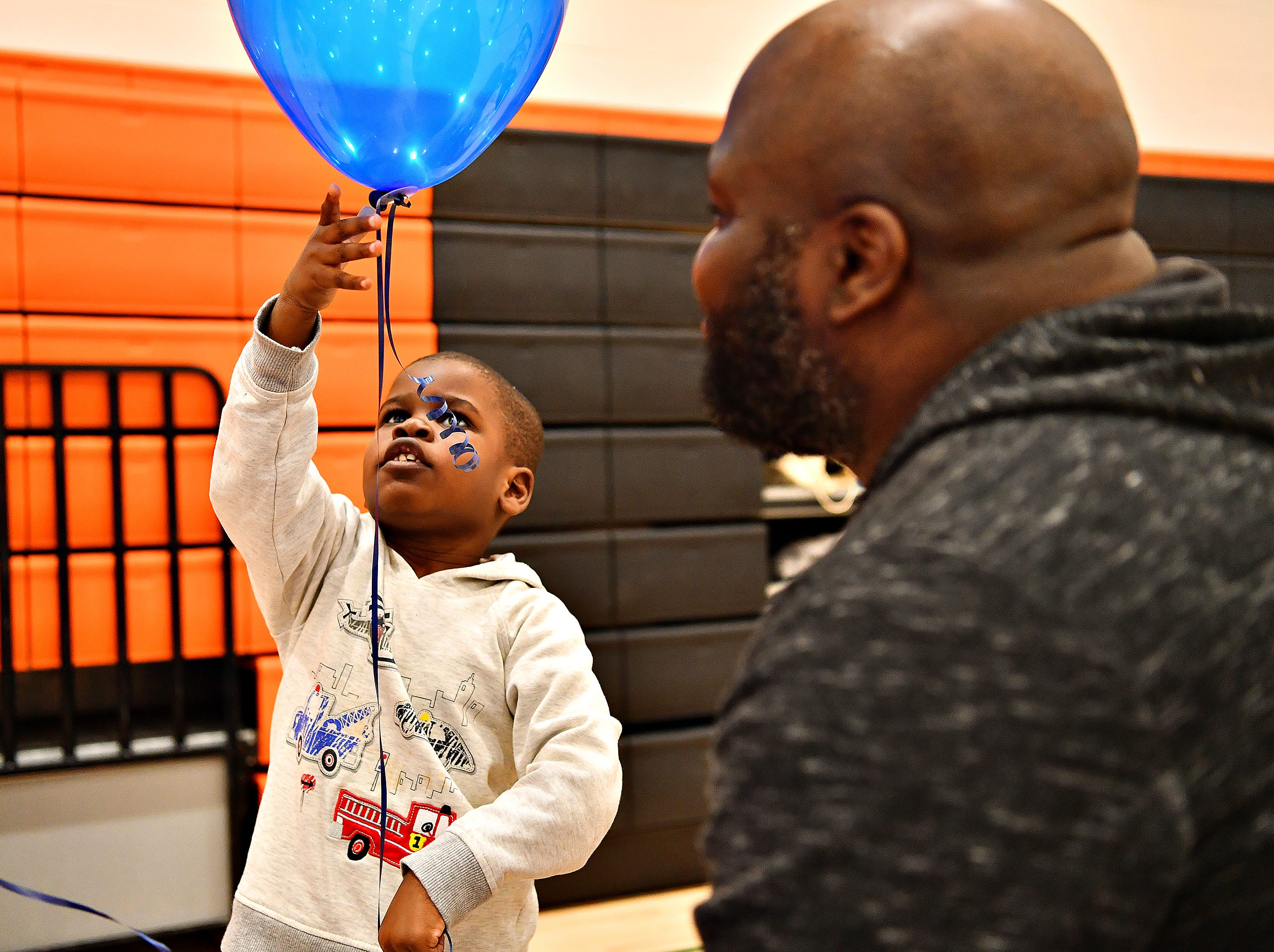 Olu Akinsola, right, of Springettsbury Township, watches his son, Diran Akinsola, 4, play with a balloon during the 2019 Walk for Autism & Autism Expo at Central York High School in Springettsbury Township, Saturday, April 6, 2019. Dawn J. Sagert photo