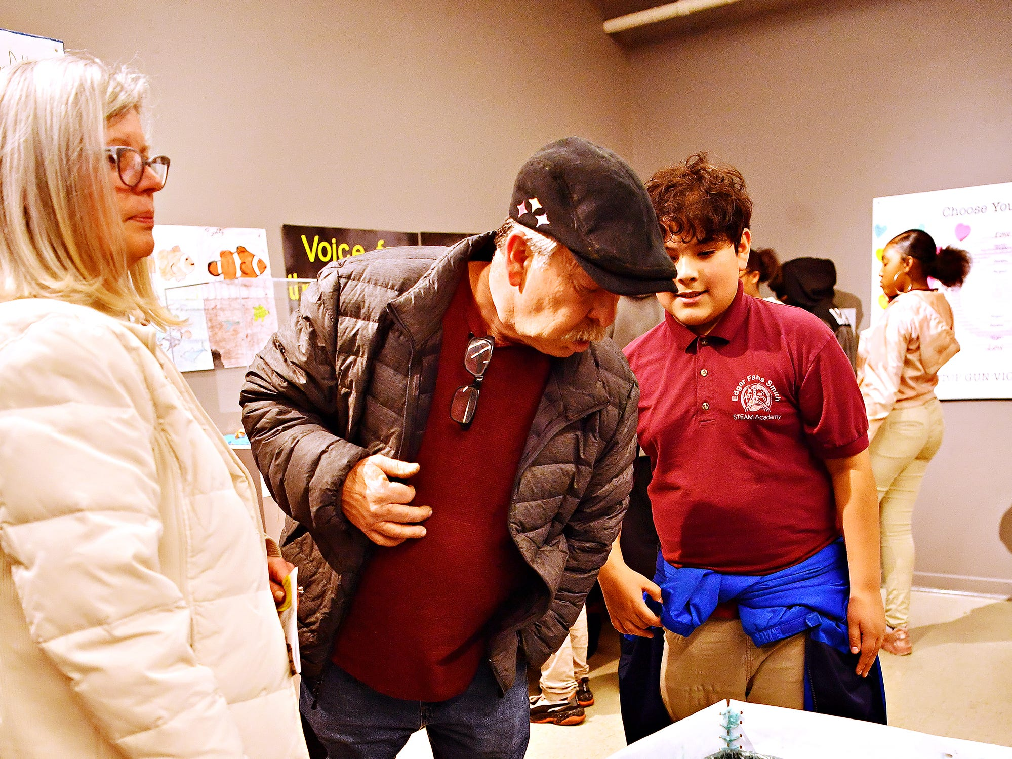 "From left, Robin Hotaling and Larry Schultz, both of Springettsbury Township, talk to Edgar Fahs Smith STEAM Academy sixth-grader Fabian Pineda, 12, about his group project, ""Paintings that Prevent Pollution"" during the school's Conflict & Change!! exhibit at Marketview Arts during First Friday in York City, Friday, April 5, 2019. Dawn J. Sagert photo"