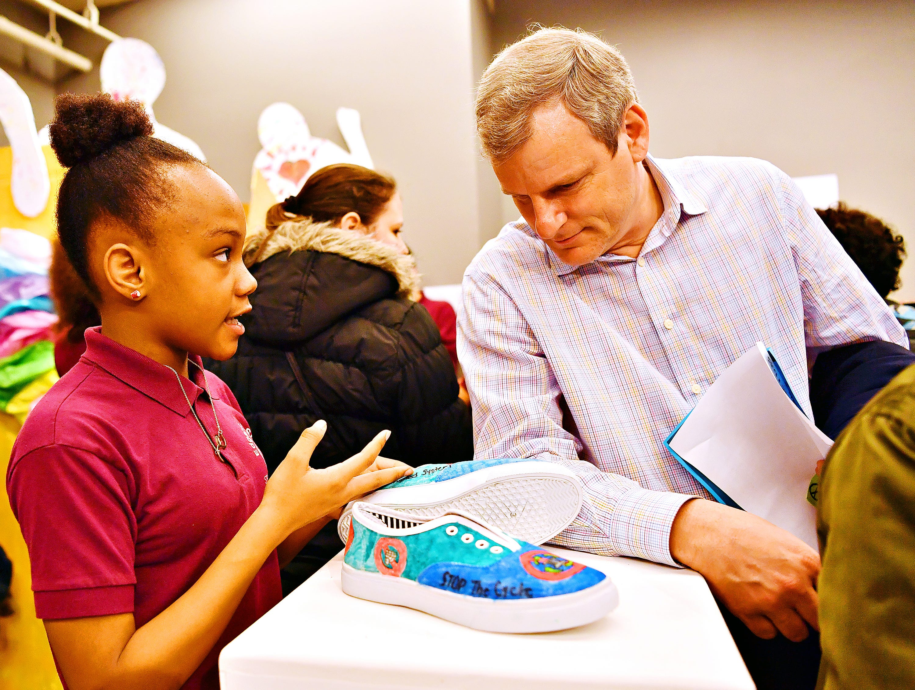 "Edgar Fahs Smith STEAM Academy fifth-grader Sayani Stokes, 11, left, explains her project, ""Corrupted"" to York City Mayor Michael Helfrich during the school's Conflict & Change!! exhibit at Marketview Arts during First Friday in York City, Friday, April 5, 2019. Dawn J. Sagert photo"