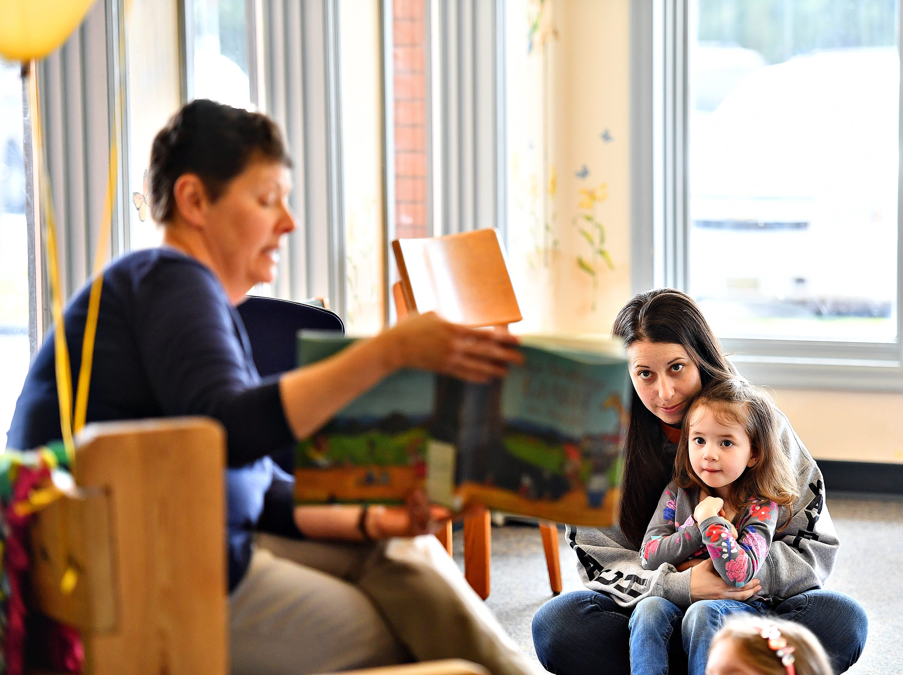 Sarah Leonard,  back right, of North Codorus Township, holds her daughter Emma Leonard, 3, as they attentively listen to Glatfelter Memorial Library Board Vice President Ann Seitz-Brown as she reads during the Annual Read-a-thon event in Spring Grove, Saturday, April 6, 2019. Dawn J. Sagert photo