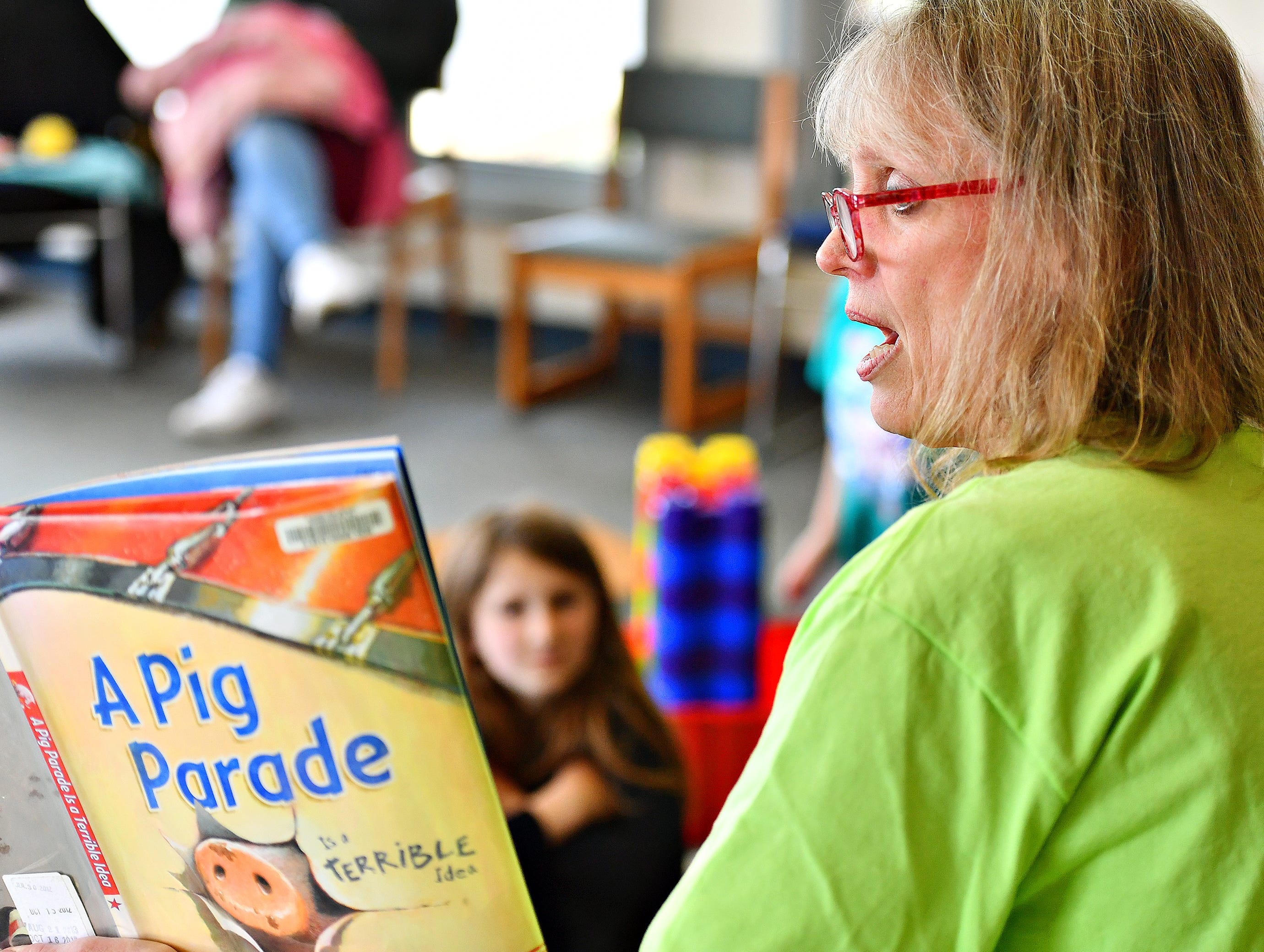 "Glatfelter Memorial Library Board Member Betsy Scheivert reads, ""A Pig Parade is a Terrible Idea,"" written by Michael Ian Black, during the Annual Read-a-thon event at the library in Spring Grove, Saturday, April 6, 2019. Dawn J. Sagert photo"
