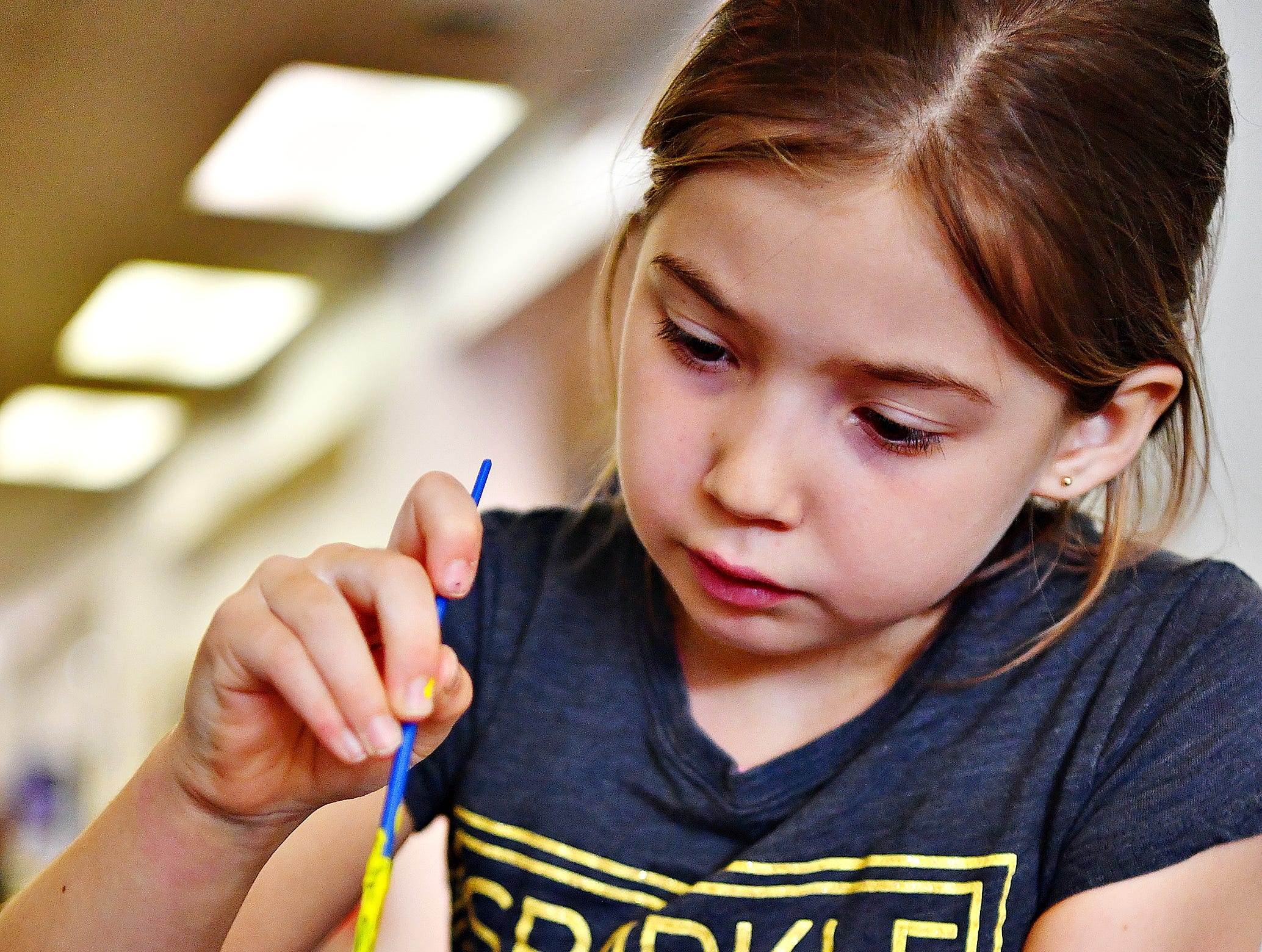 Marcey Neiderer, 8, of Jackson Township, paints a daffodil at a craft table during Glatfelter Memorial Library's Annual Read-a-thon event in Spring Grove, Saturday, April 6, 2019. Dawn J. Sagert photo