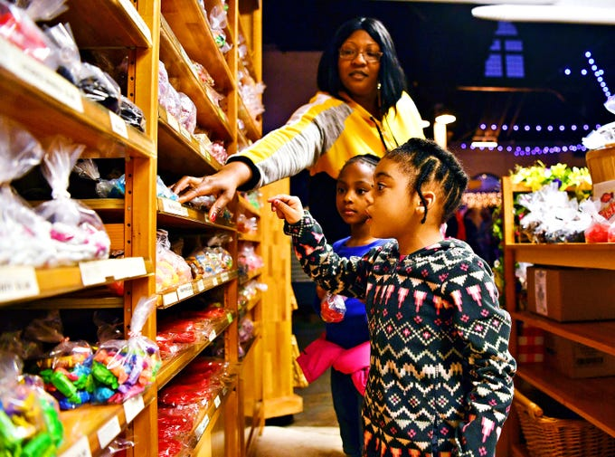 Davia Criswell, back, of York City, guides her daughters LaVaya Criswell, center, and LaJoy Criswell, both 4, to the blue sharks at T.K.'s Nuts and Candies at Central Market on First Friday in York City, Friday, April 5, 2019. Dawn J. Sagert photo