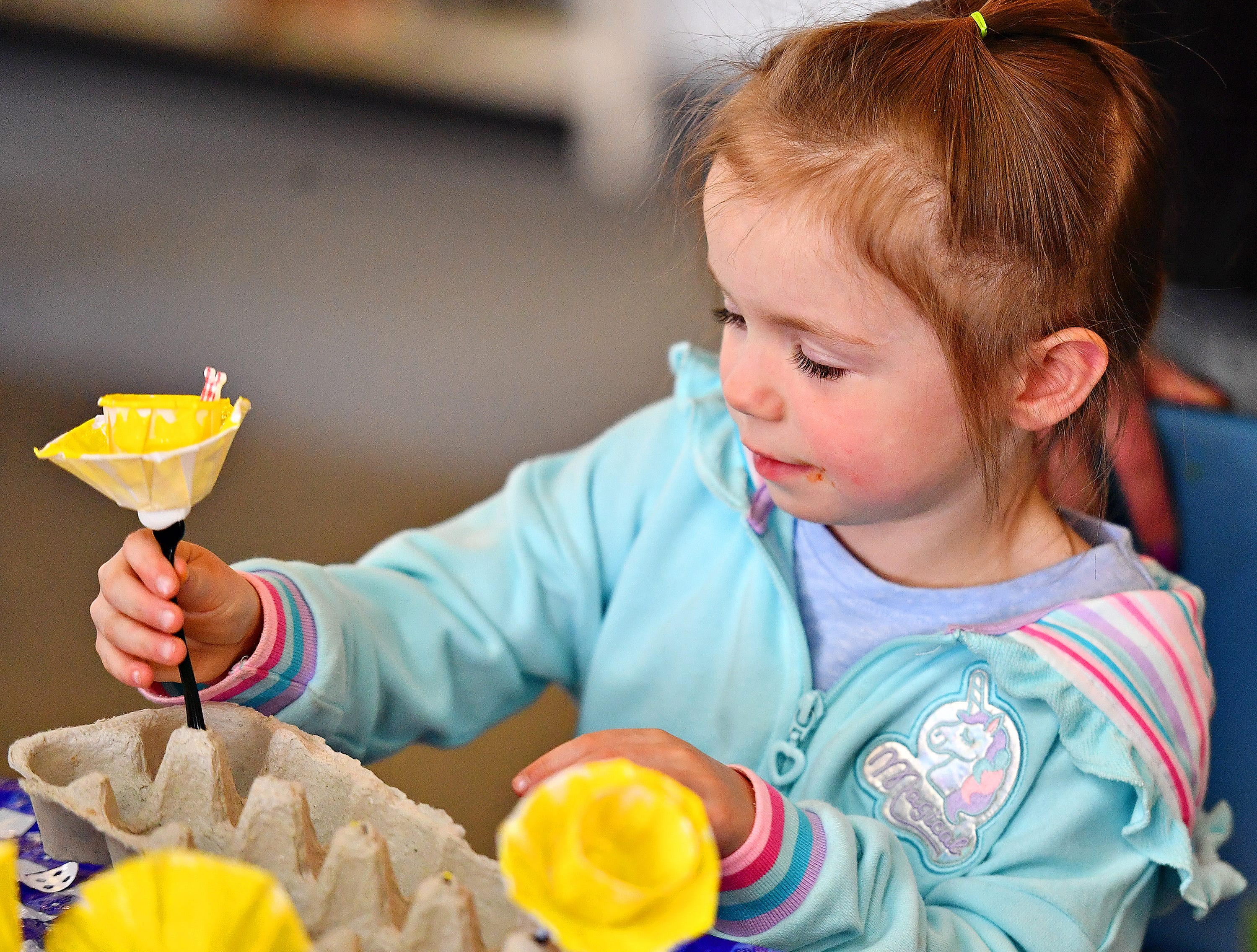 Nevaeh Bortner Waltz, 4, places a freshly-painted daffodil into a holder during the Glatfelter Memorial Library's Annual Read-a-thon event in Spring Grove, Saturday, April 6, 2019. Dawn J. Sagert photo