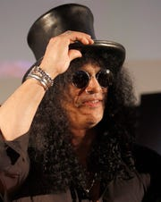 In this April 22, 2010, file photo, former Guns N' Roses guitarist Slash greets fans during an event in Tokyo, Japan.  The former wife of Guns N' Roses guitarist Slash is selling off exotic and erotic items from their 14 years of marriage. Julien's Auctions on Thursday, April 3, 2019  announced the collection from Slash and Perla Hudson's Beverly Hills estate will be part of next month's Music Icons auction.