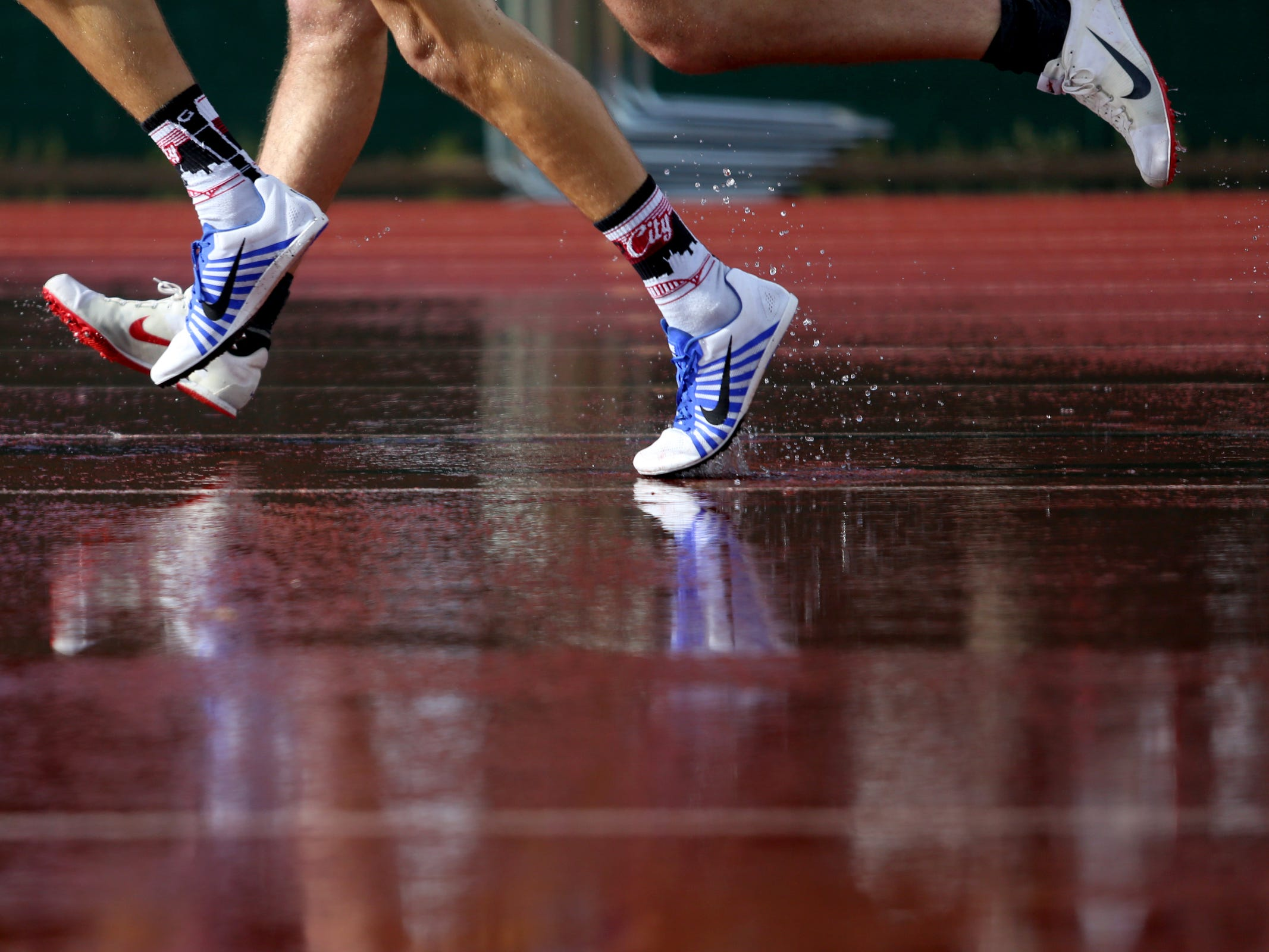Competitors in the boys 1500 meter run race through puddles during the Titan Track Classic high school track and field meet at West Salem High School on April 5, 2019.