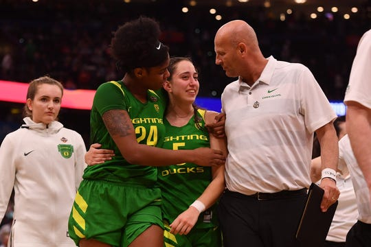 Oregon Ducks guard Maite Cazorla (5), Ducks forward Ruthy Hebard (24), and Ducks head coach Kelly Graves (right) react while walking off the court after their game against the Baylor Lady Bears in the semifinals of the women's Final Four of the 2019 NCAA Tournament at Amalie Arena.