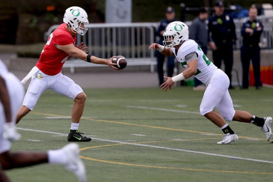 Tyler Shough (12) hands the ball off to Travis Dye (26) during the Oregon Ducks spring football practice and scrimmage at Hillsboro Stadium on April 6, 2019.