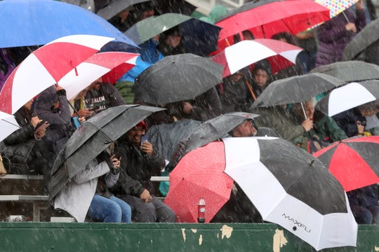 Fans use umbrellas as rain and hail fall during the Titan Track Classic high school track and field meet at West Salem High School on April 5, 2019.