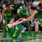 Oregon forward Oti Gildon (32), guard Maite Cazorla, right, and forward Ruthy Hebard (24) help guard Sabrina Ionescu off the court during the first half of a Final Four semifinal against Baylor in the NCAA women's college basketball tournament Friday, April 5, 2019, in Tampa, Fla.