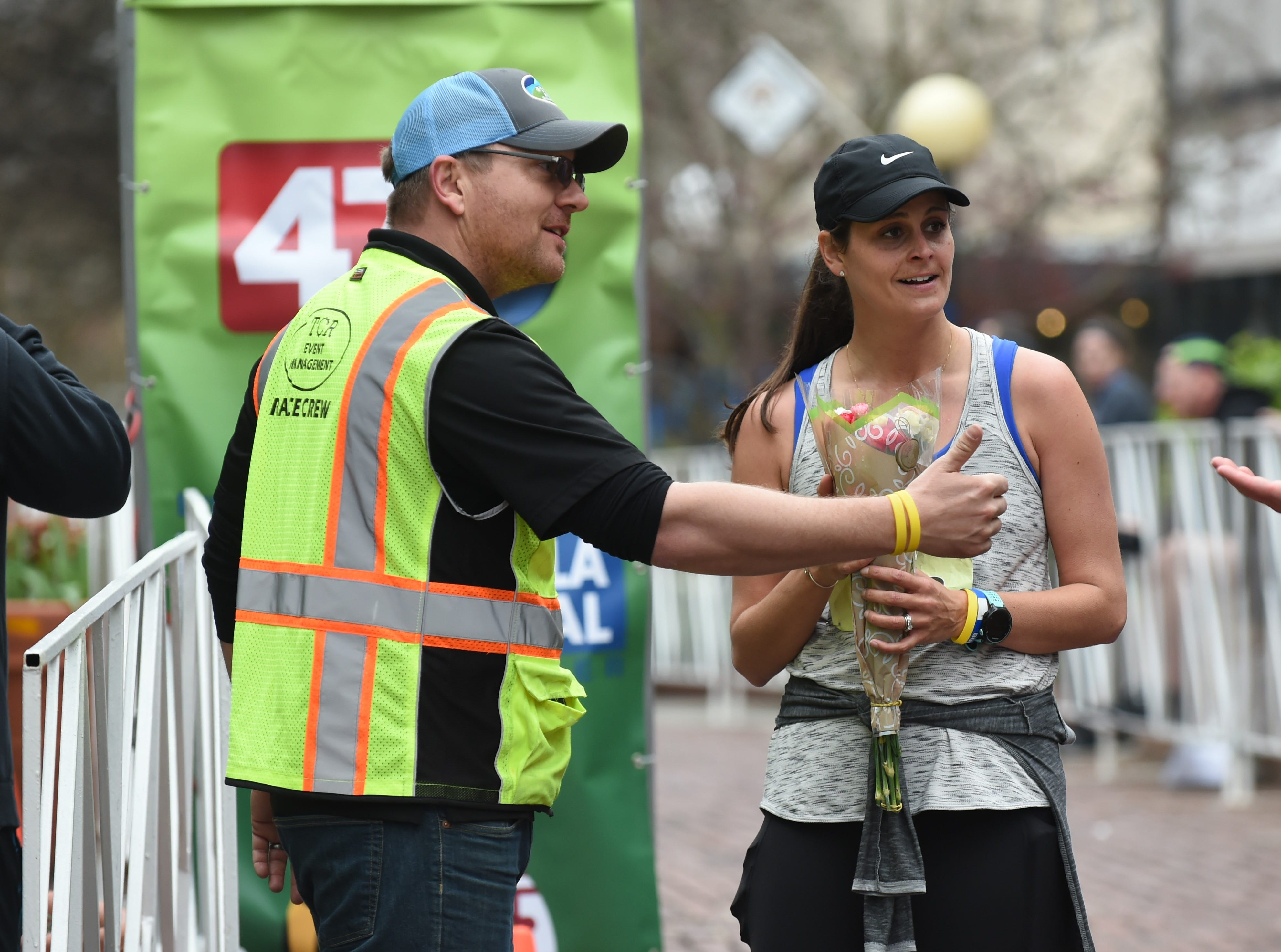 Janel Walters is presented with flowers after finishing the half marathon at the 2nd Salisbury Marathon/ Half Marathon/ 5k on Saturday, April 6, 2019. They were sent from her husband who couldn't attend the event due to military obligations.