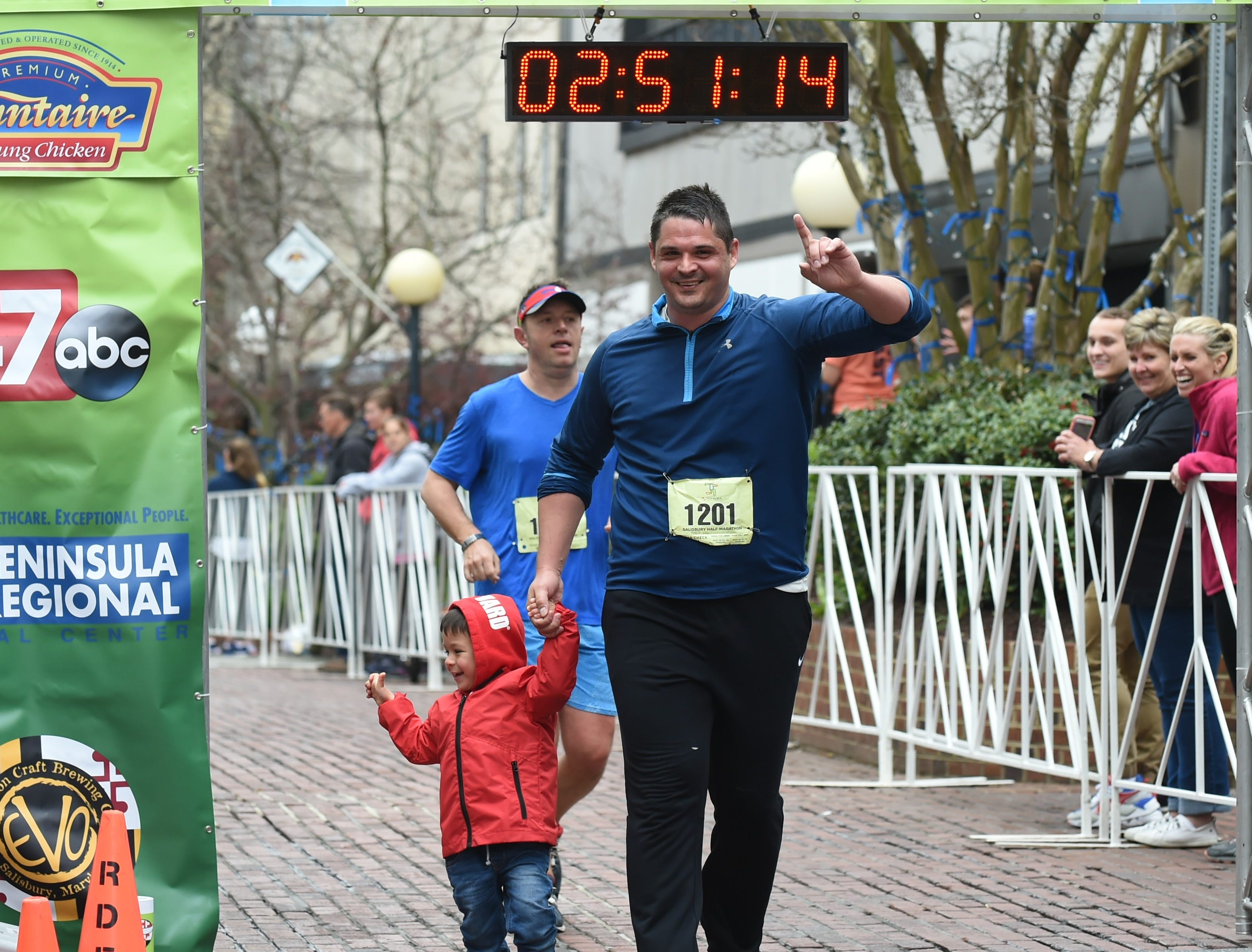 Andrew Davis crosses the finish line with his son after running in the 2nd Salisbury Marathon/ Half Marathon/ 5k on Saturday, April 6, 2019.