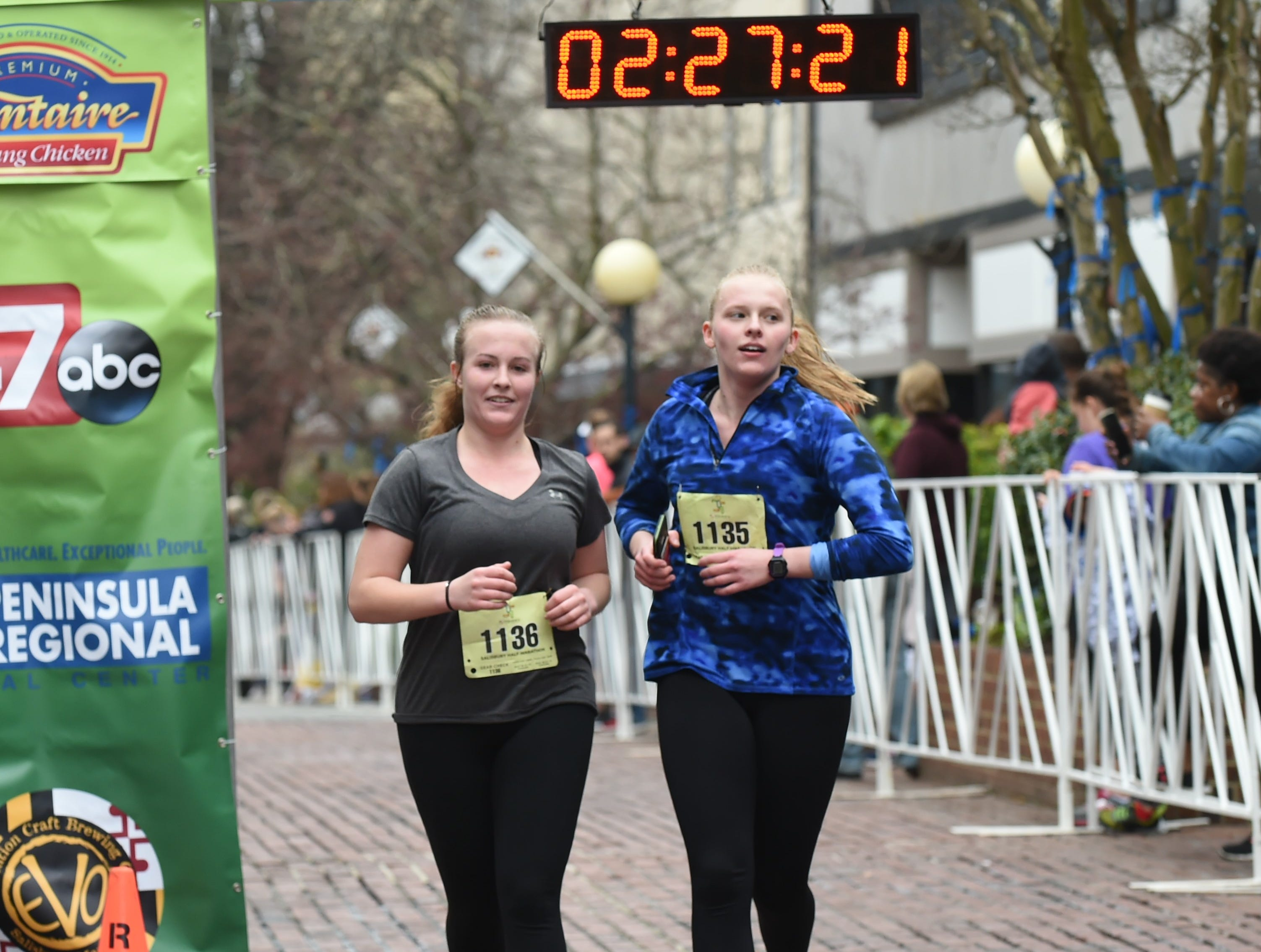 Caroline Copes (left) and Mallory Boyd cross the finish line after running the half marathon at the 2nd Salisbury Marathon/ Half Marathon/ 5k on Saturday, April 6, 2019.