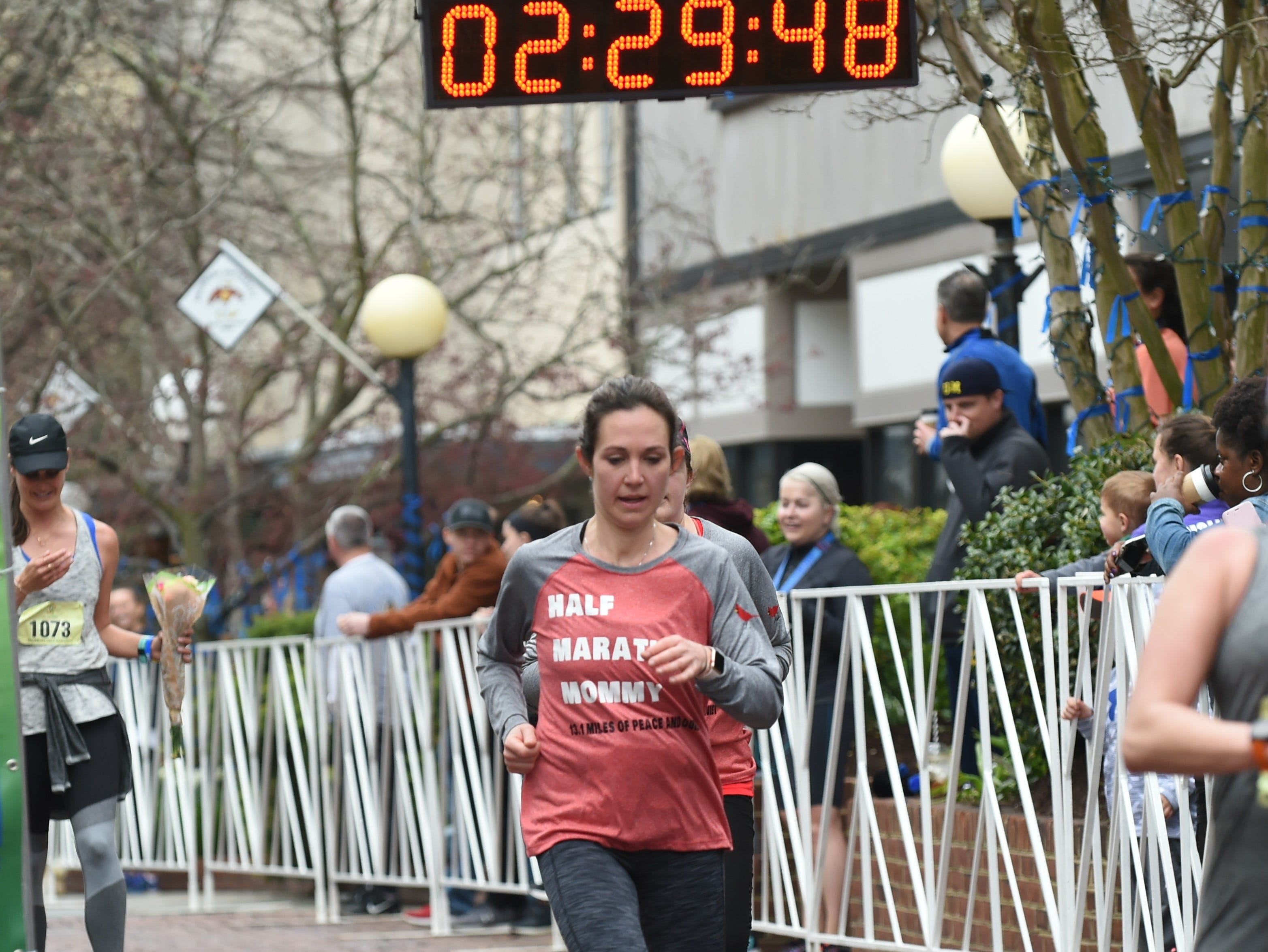 "A runner with a shirt that reads ""Half Marathon Mommy"" crosses the finish line at the 2nd Salisbury Marathon/ Half Marathon/ 5k on Saturday, April 6, 2019."
