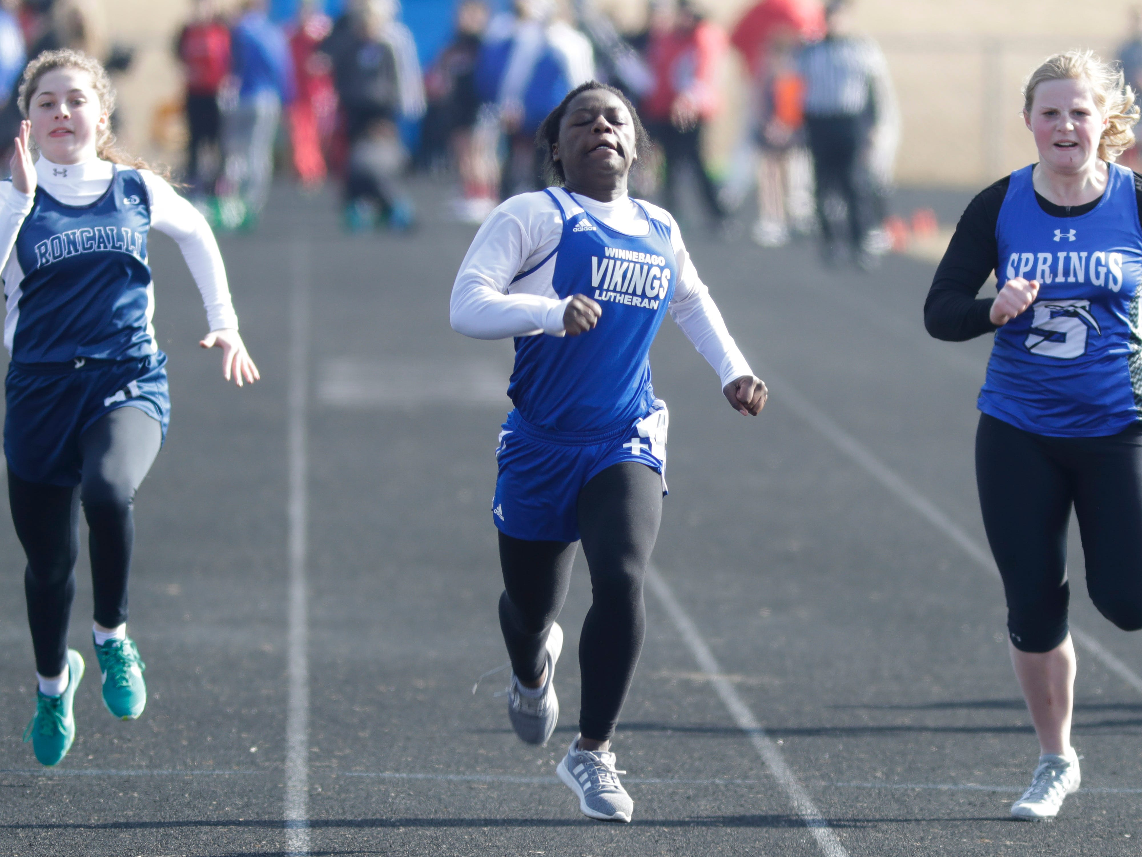 Roncalli's Jayme Jirokovic, left, Winnebago Lutheran's Diamond Lange and St. Mary Springs' Peyton Hyland, run a heat in the 100 meter dash at the Flying Dutchmen Invite, Friday, April 5, 2019, in Oostburg, Wis.