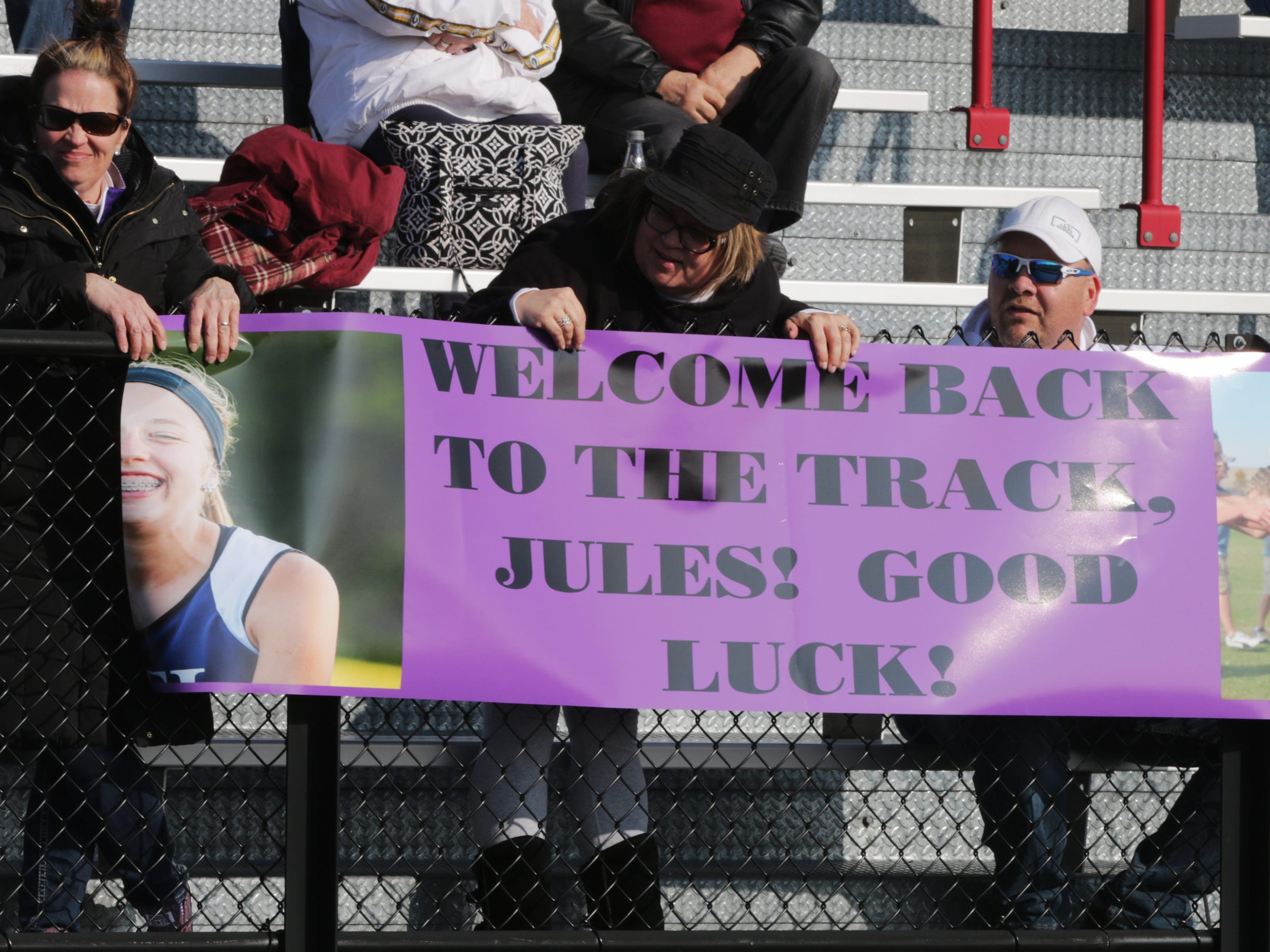 Family members of Julia Koenig proudly held a banner as Koenig ran her first event after being cleared to run following ACL surgery, Friday, April 5, 2019, in Oostburg, Wis.