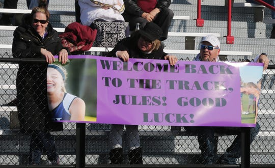 Family members of Julia Koenig proudly held a banner as Koenig ran her first event after being cleared to run following ACL surgery on April 5 in Oostburg.
