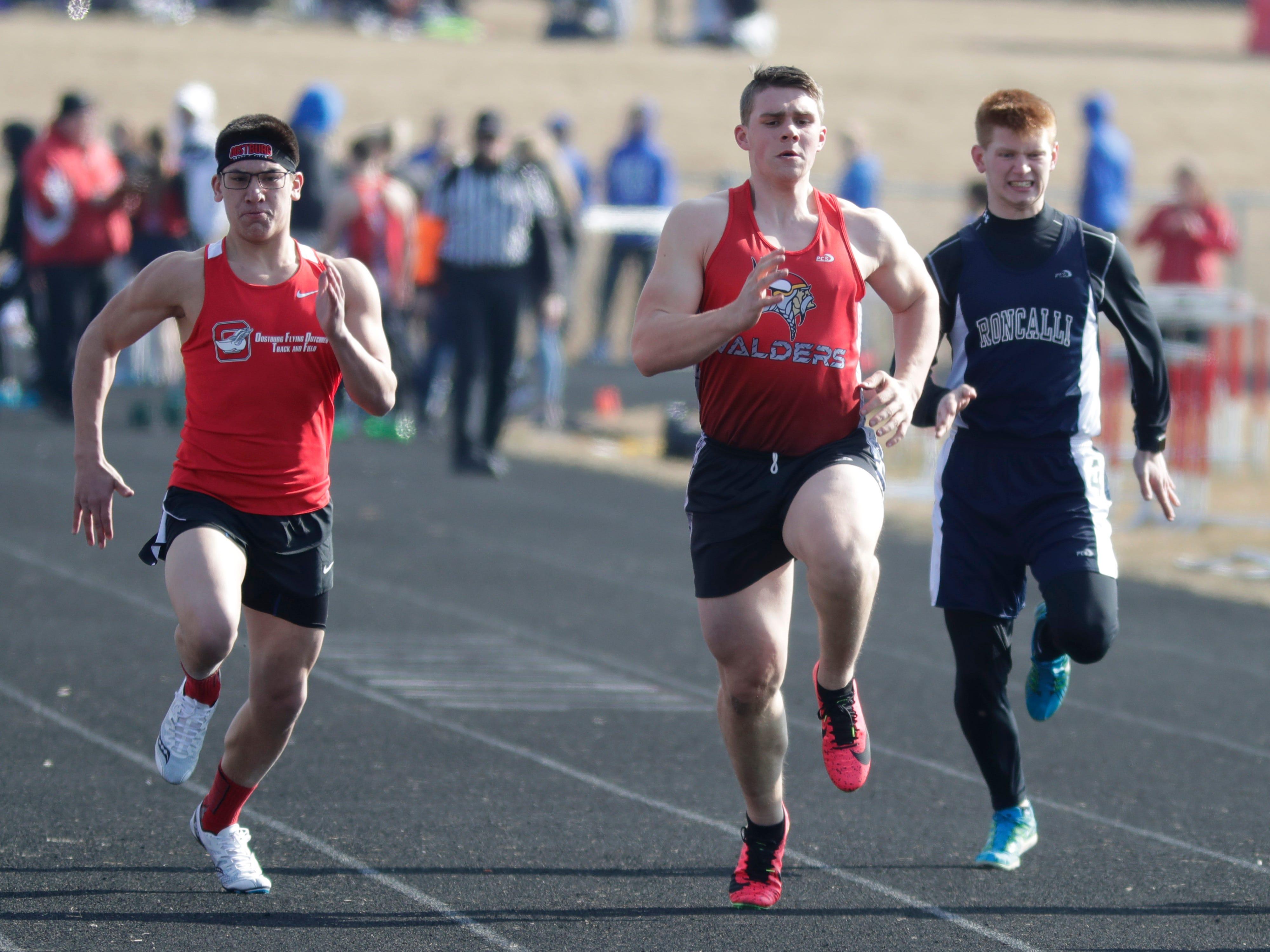 Oostburg's Ethan Wittenben, left, Valders' Andrew Welch and Roncalli's Matt Koch compete in the 100 meter dash, Friday, April 5, 2019, in Oostburg, Wis.