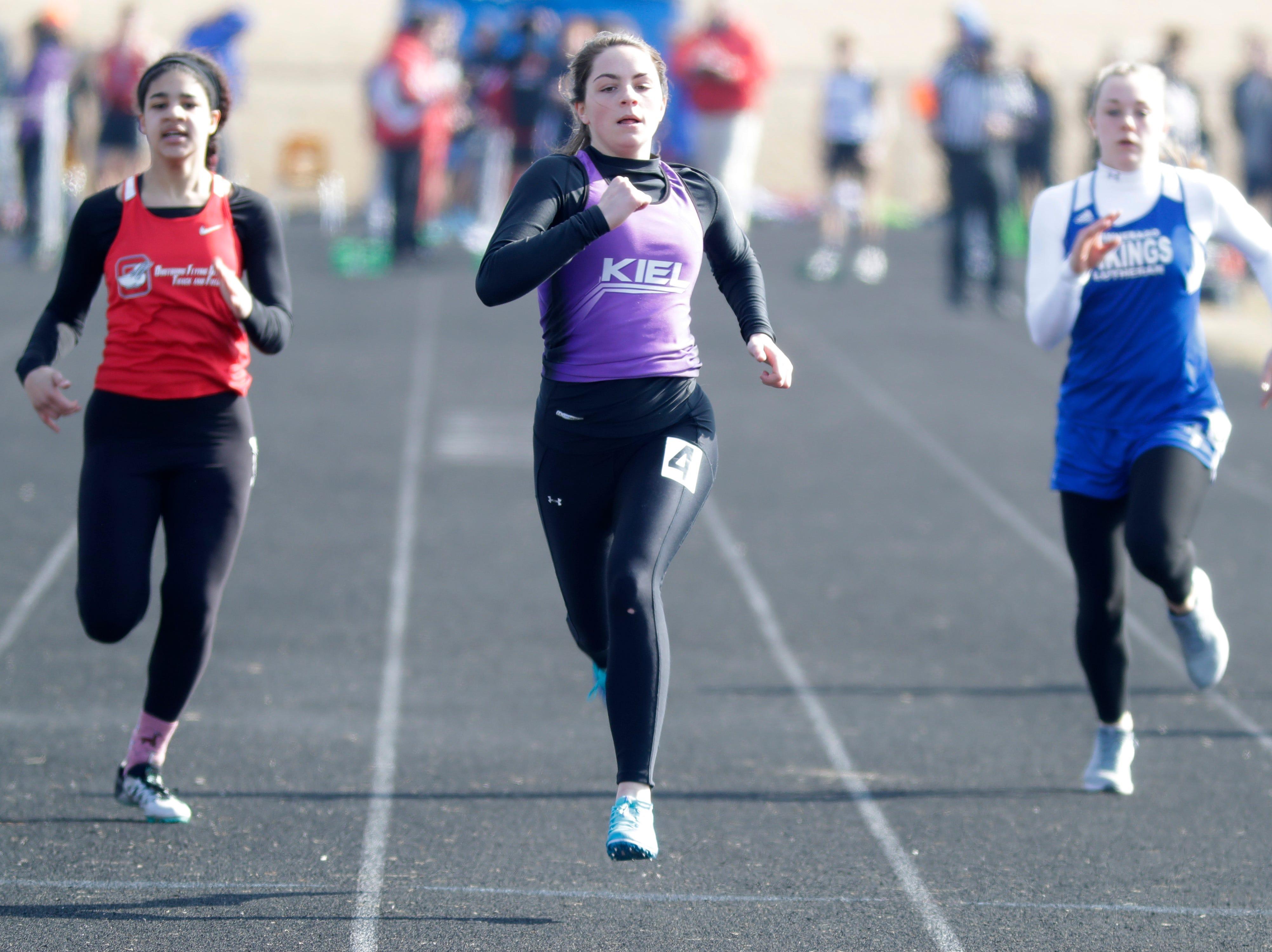 Oostburg's Monica Mentink, left, Kiel's Holly Vogel, center, and Winnebago Lutheran's Peyton Kemnitz compete in the 100 meter dash, Friday, April 5, 2019, in Oostburg, Wis.