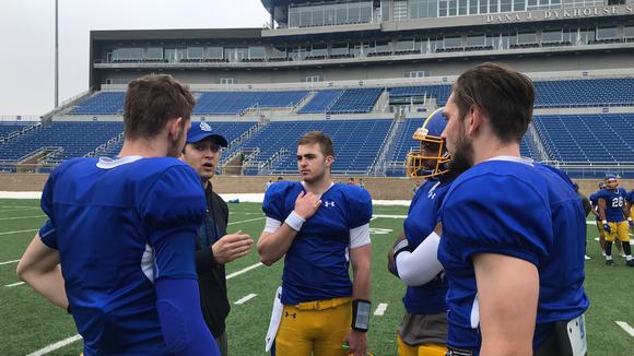 SDSU quarterbacks coach Zach Lujan talks with (from left) Matt Connors, Kurt Walding, J'Bore Gibbs and Kanin Nelson at Saturday's practice