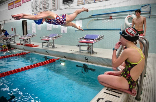 Apollo Boys Swim and Dive Team coach Alex Badger demonstrates a technique during Eagles Swim Camp Wednesday, April 3, at Apollo High School in St. Cloud.