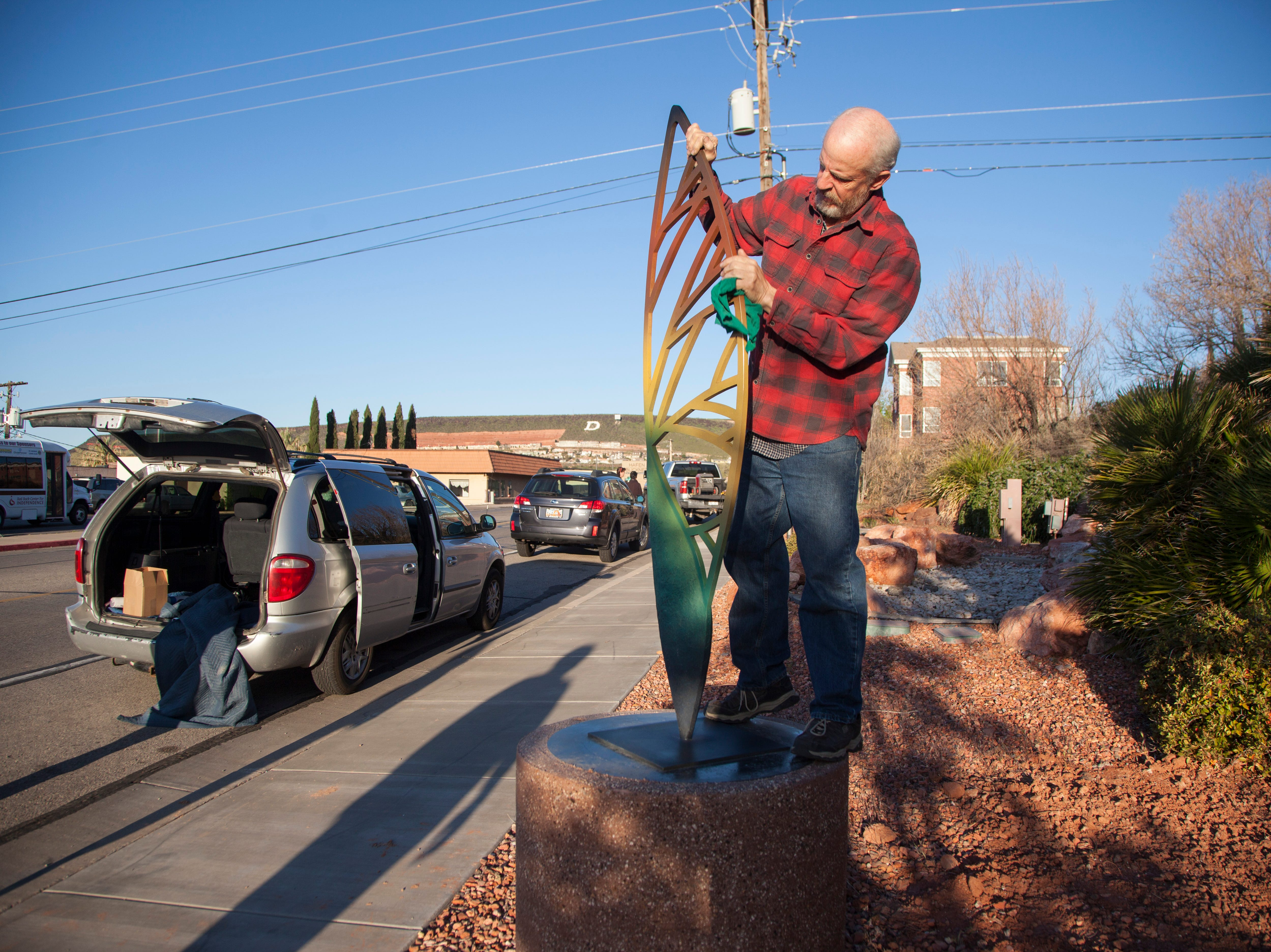 Artists and city workers install art around downtown St. George Saturday, April 6, 2019.