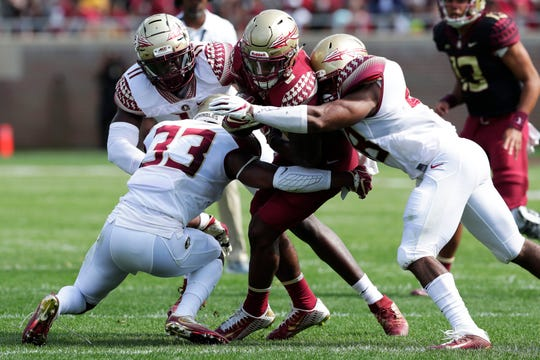 Florida State Seminoles running back Cam Akers (3) gets tackled by three defenders. Florida State hosts its Garnet and Gold Spring Game Saturday, April 6, 2019.