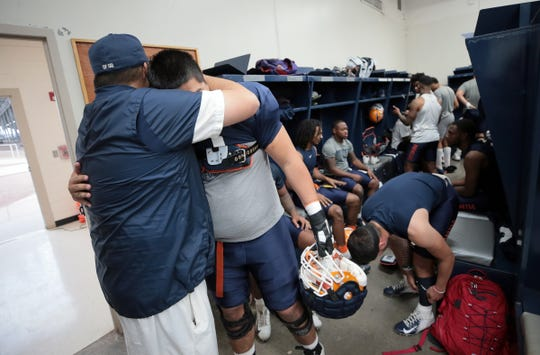 Del Valle head football coach Jesse Perales hugs his former player, who now plays for UTEP, Tristan Tuialuuluu before the Miners' practice at Del Valle High School on Friday, April 5, 2019.