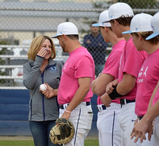 Central Valley Christian High School baseball coach Shane Marshall hands his mother, Stacey, the game ball on Friday in a Central Sequoia League contest. Stacey was diagnosed with breast cancer in December 2018.