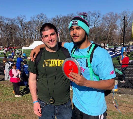 Ramapo coach Jason Zweig with Anthony Harrison after Harrison's Section 1-record discus throw.