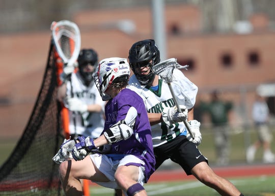 Yorktowns defenseman Keith Boyer (13) works John Jay-Cross River's Bryce Ford (9) during their 8-3 win over John Jay-Cross River in boys lacrosse at Yorktown High School in Yorktown on Saturday, April 6, 2019.