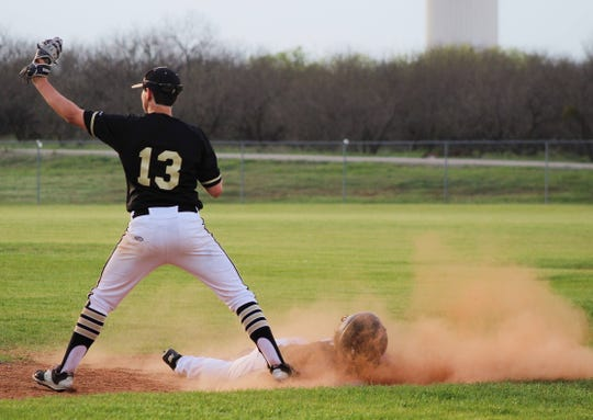 Henrietta's Landry Bennett catches the ball to keep a City View runner from stealing a base.