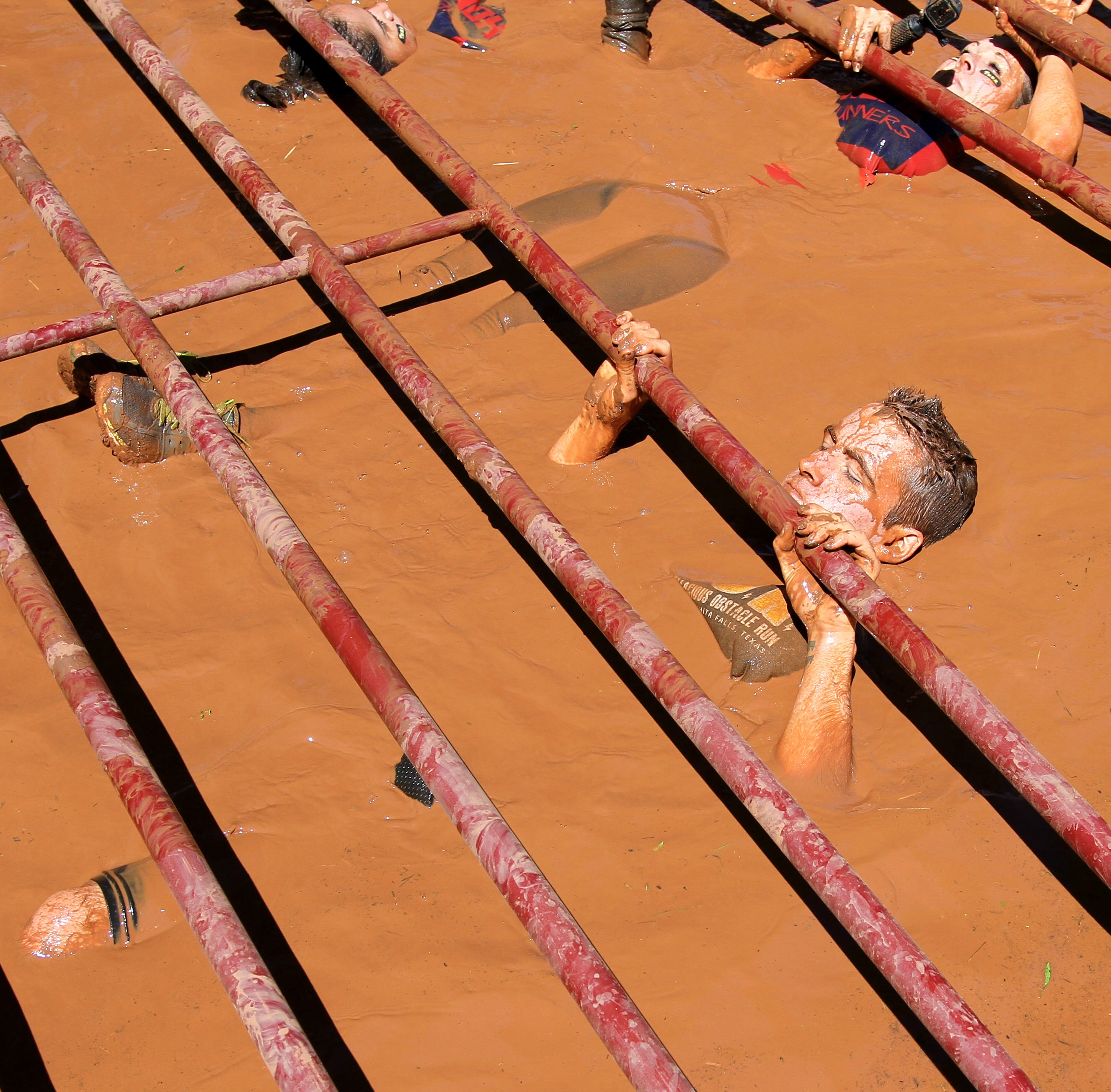Runners play in the mud in Texoma's Hellacious Obstacle Run
