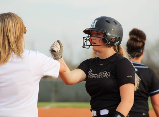 Henrietta's Kalico Burkes fist bumps her coach after making it to first base in the Ladycats' game against the City View Mustangs.