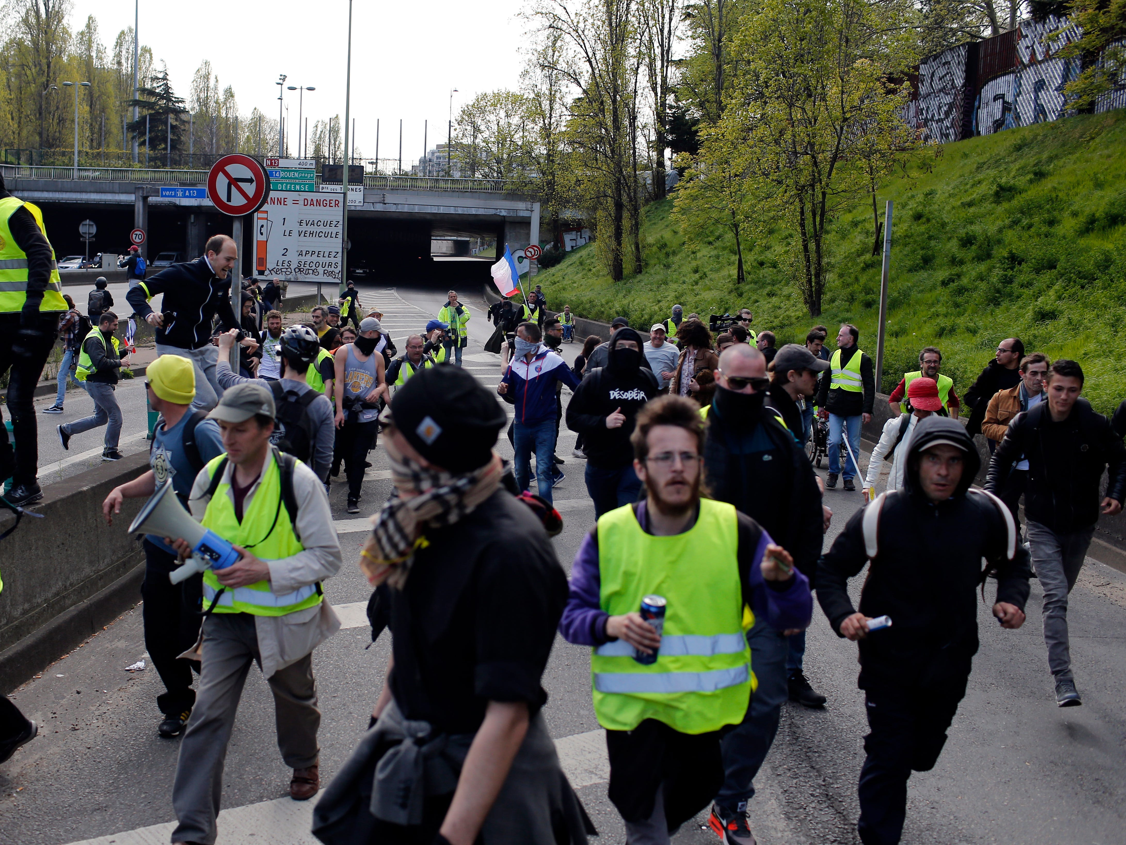 Protesters run from the police after an attempt to block the highway at Porte de Champerret in Paris, France, Saturday, April 6, 2019. Protesters from the yellow vest movement are taking to the streets of France for a 21st straight weekend, with hundreds gathered for a march across Paris, one of numerous protests around the country.