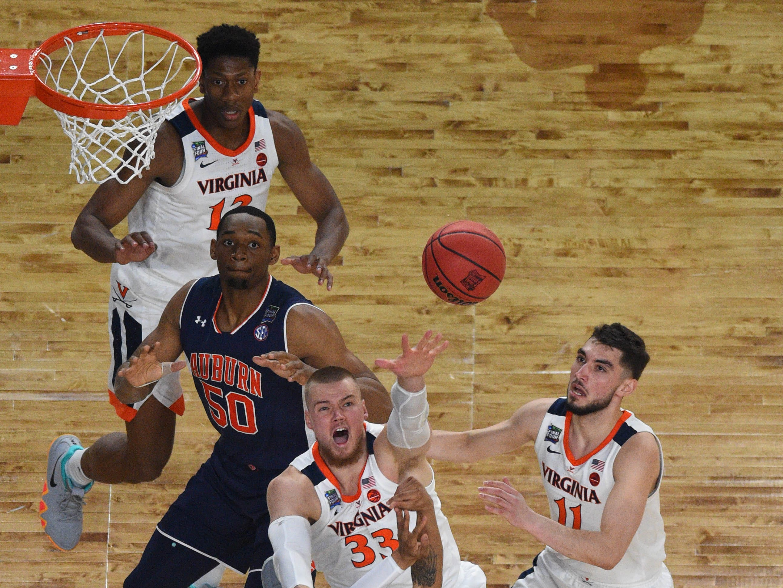 Virginia Cavaliers center Jack Salt (33) blocks the shot of Auburn Tigers guard Samir Doughty (10).