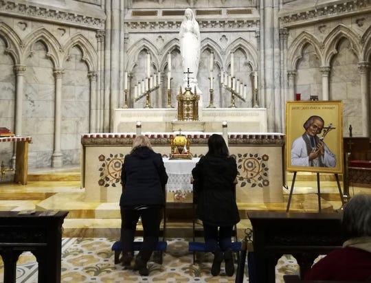 Two women pray in front a container bearing the heart of St. John Vianney on April 6, 2019 at St. Patrick's Cathedral in New York. The 150-year-old heart of the French priest is being toured throughout the United States. The tradition of venerating the body parts of saintly Catholics goes back to the Middle Ages in Italy.