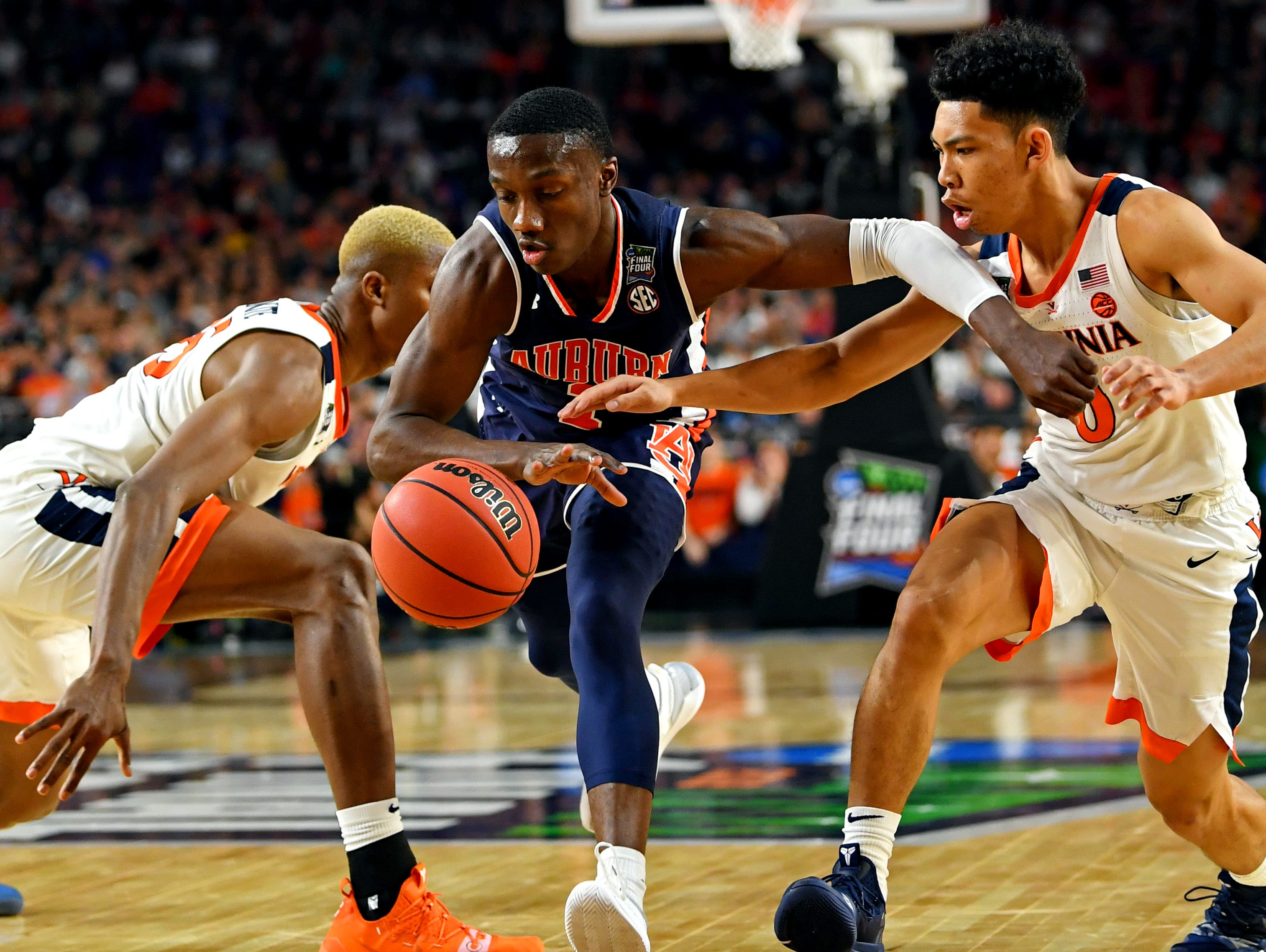Auburn Tigers guard Jared Harper (1) drives to the basket against the Virginia Cavaliers.
