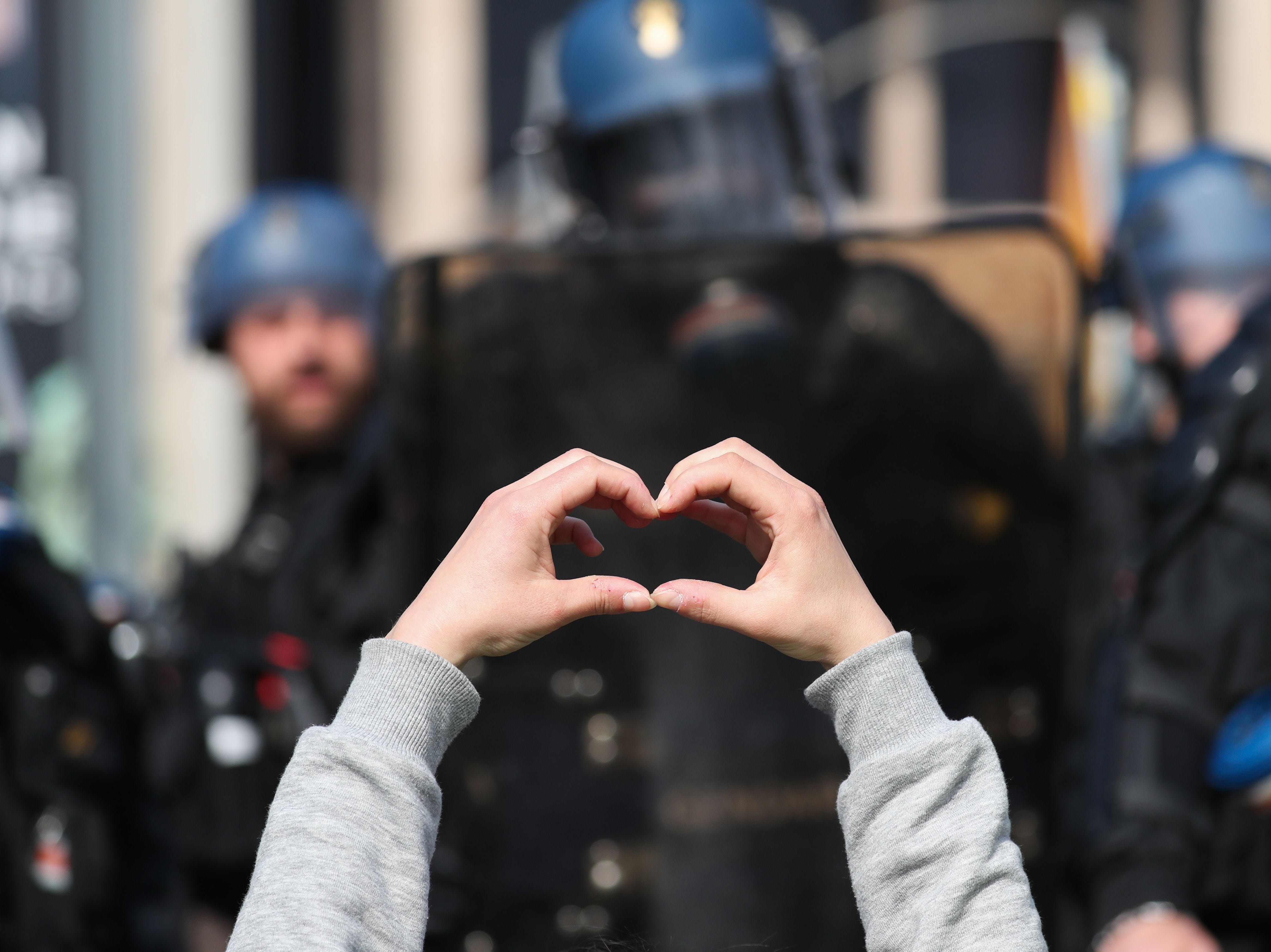 "A protester makes a heart-shaped gesture with their hands at riot police officers during a ""Yellow Vests"" (Gilets Jaunes) protest in Rouen on April 6, 2019 as demonstrations are planned by the ""Yellow Vest"" movement for the 21st consecutive Saturday."