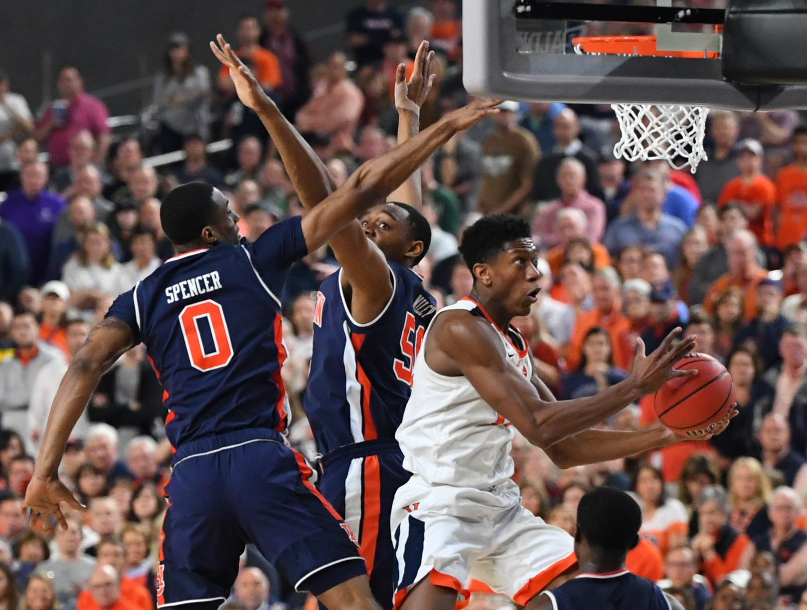 Auburn Tigers guard J'Von McCormick (12) shoots between Auburn Tigers forward Horace Spencer (0) and center Austin Wiley (50).
