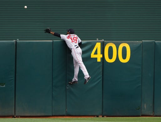 April 4:  Boston's Jackie Bradley Jr. (19) jumps onto the fence but is unable to make a catch on an Oakland three-run home run.