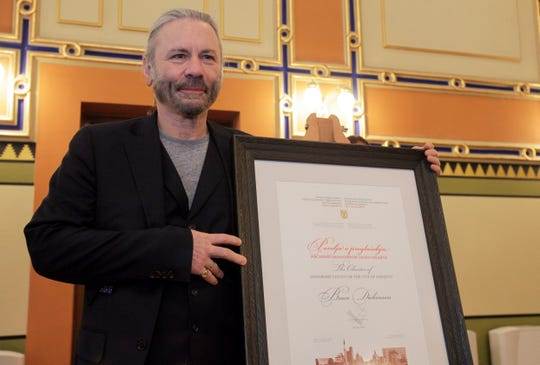 Bruce Dickinson poses for cameras with his honorary citizen certificate at the city hall in Sarajevo, Bosnia-Herzegovina on April 6, 2019.