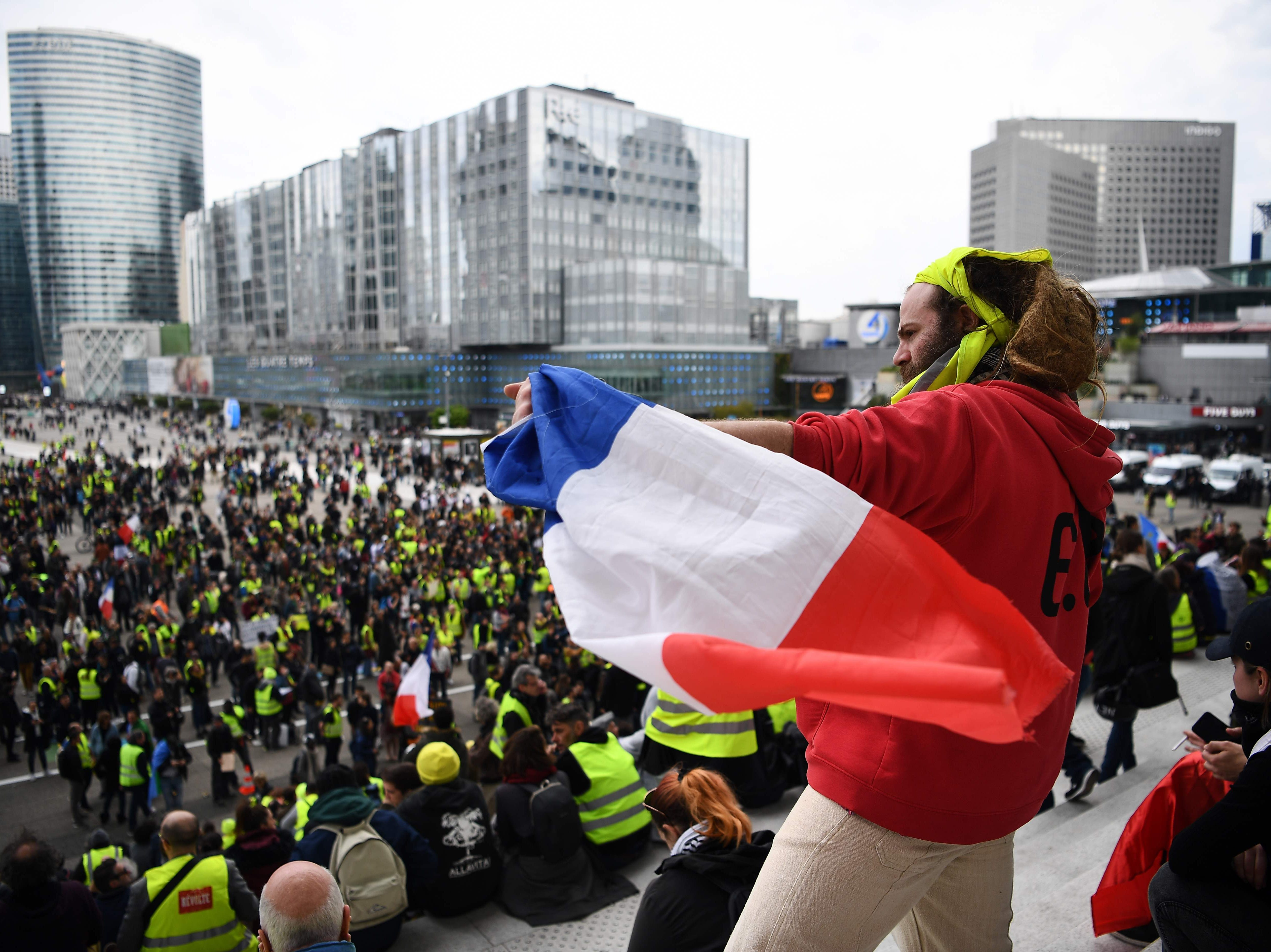 A protester holds up the French national flag as protesters gather at La Defense, west of Paris, on April 6, 2019 during a demonstration by the 'Yellow Vests' (gilets jaunes) movement on the 21st consecutive Saturday.