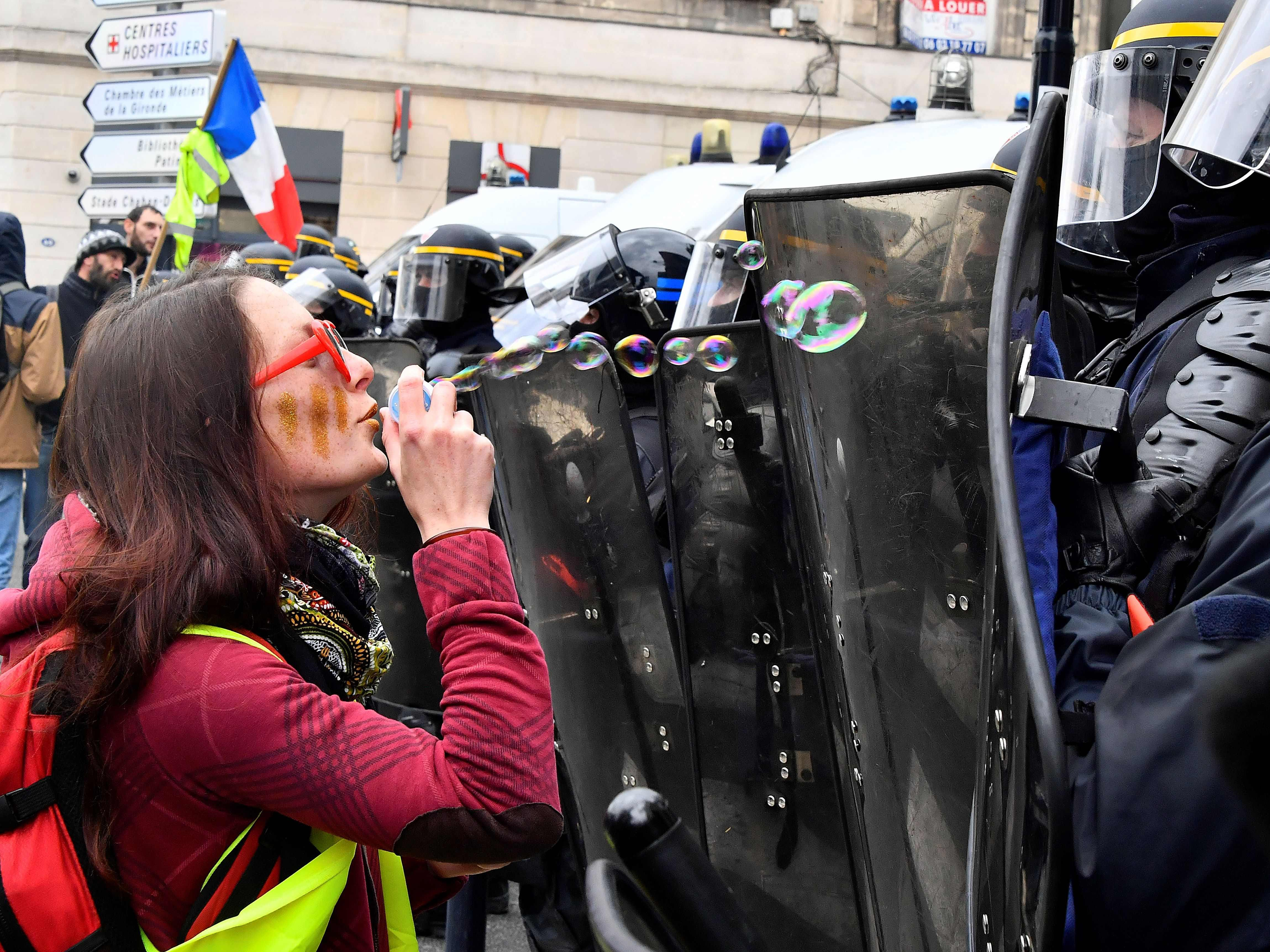 "A woman blows bubbles in front of riot police officers during a demonstration  by the ""Yellow Vest"" (Gilets Jaunes) movement for the 21st consecutive Saturday, on April 6, 2019 in Bordeaux."