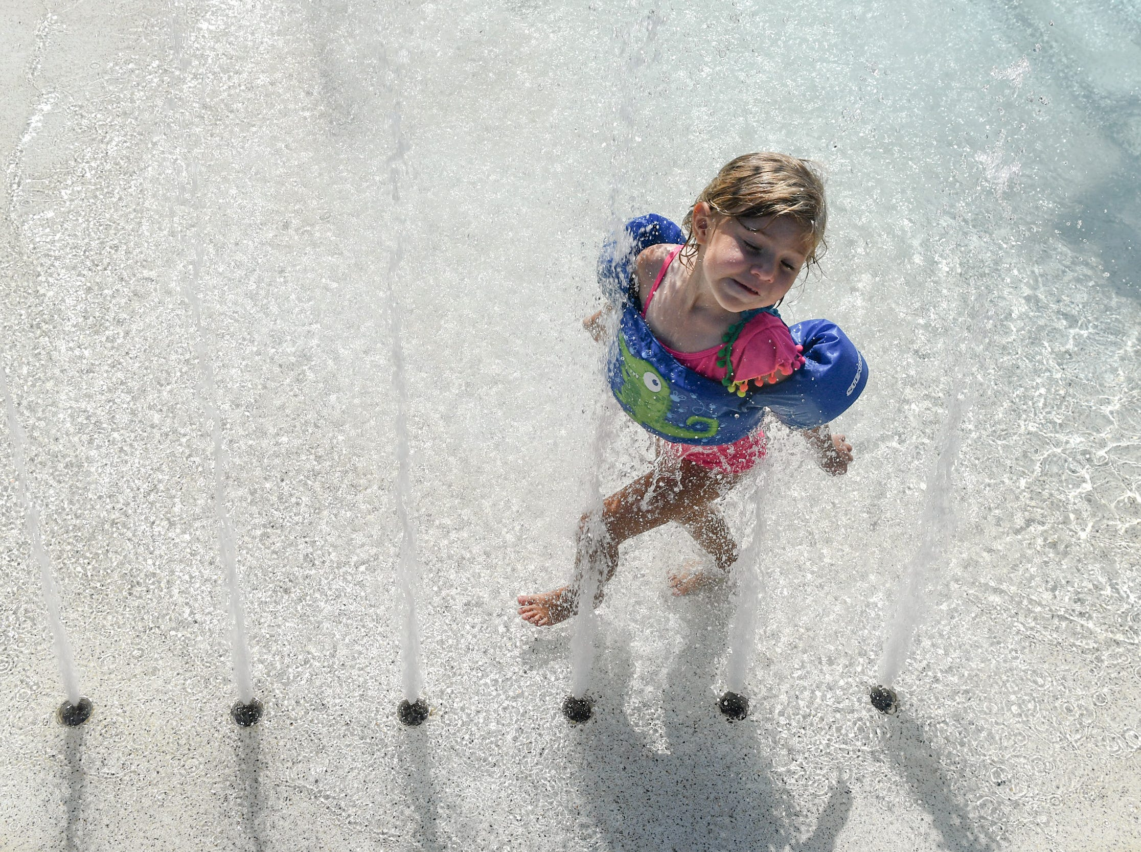 """Summertime walk"" Madelynn Pardani of Piedmont runs through water at the Anderson Area YMCA Water Works pool area in Anderson on Wednesday. The first day of summer is June 21."