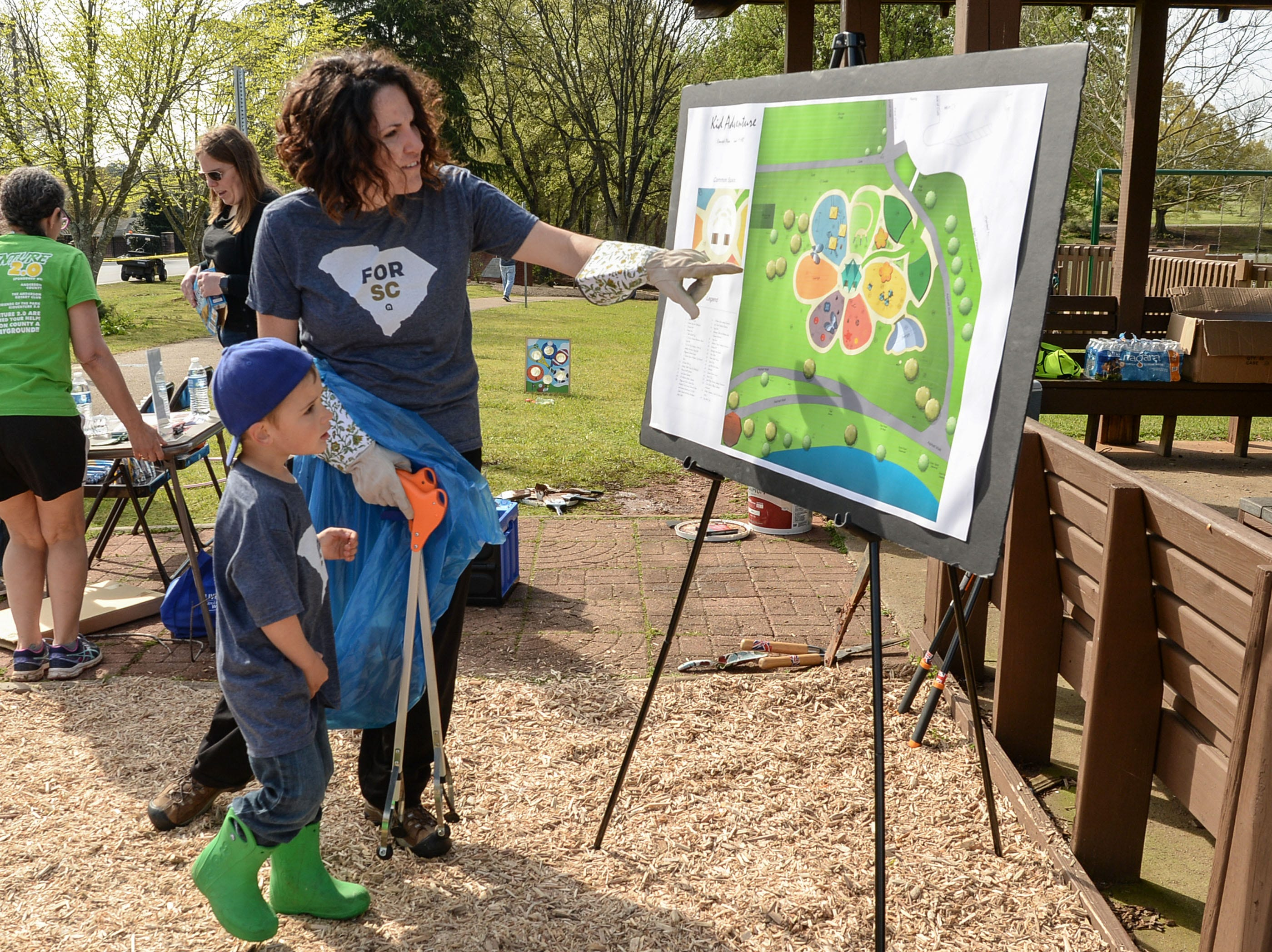 Charity Reed, and her son Jesse, 4, look at a proposed design for a new KidVenture park at the Anderson Sports and Entertainment Complex was on display during the annual spring cleanup day Saturday. A group of 310 volunteers, 250 from NewSpring Church, helped spread 100 cubic yards (70,000 pounds) of mulch, and brush 30 gallons of stain on the fences, pick up trash, and trim trees and shrubs at the park which opened 20 years ago in 1999.