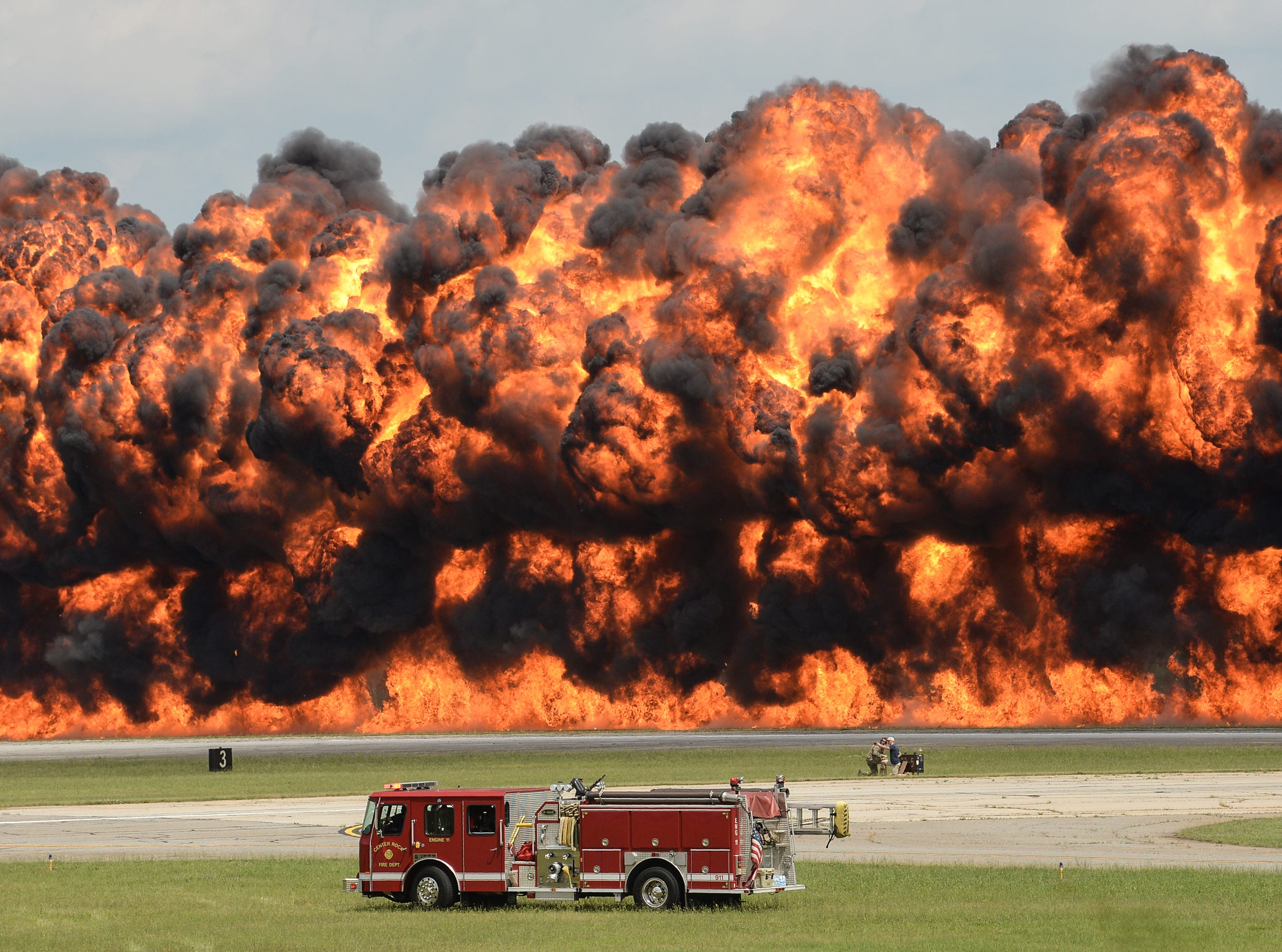 """Feel the heat"" - Center Rock fire department truck is dwarfed by the flames created by the Firewalkers International Pyrotechnics demonstration team during the Jo & Bill Trent Regional Airshow. No one was hurt in the fiery demonstration which got the crowd's approval."