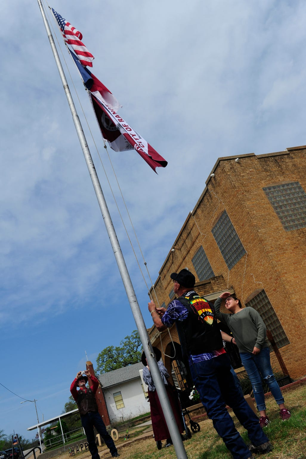 LilliyAna Hernandez, 12, shades her eyes as she watches as her flag is raised over Ranger City Hall Saturday April 6, 2019. The sixth-grader's design was chosen from 101 entries to represent the town which celebrated the centennial anniversary of its charter over the weekend.